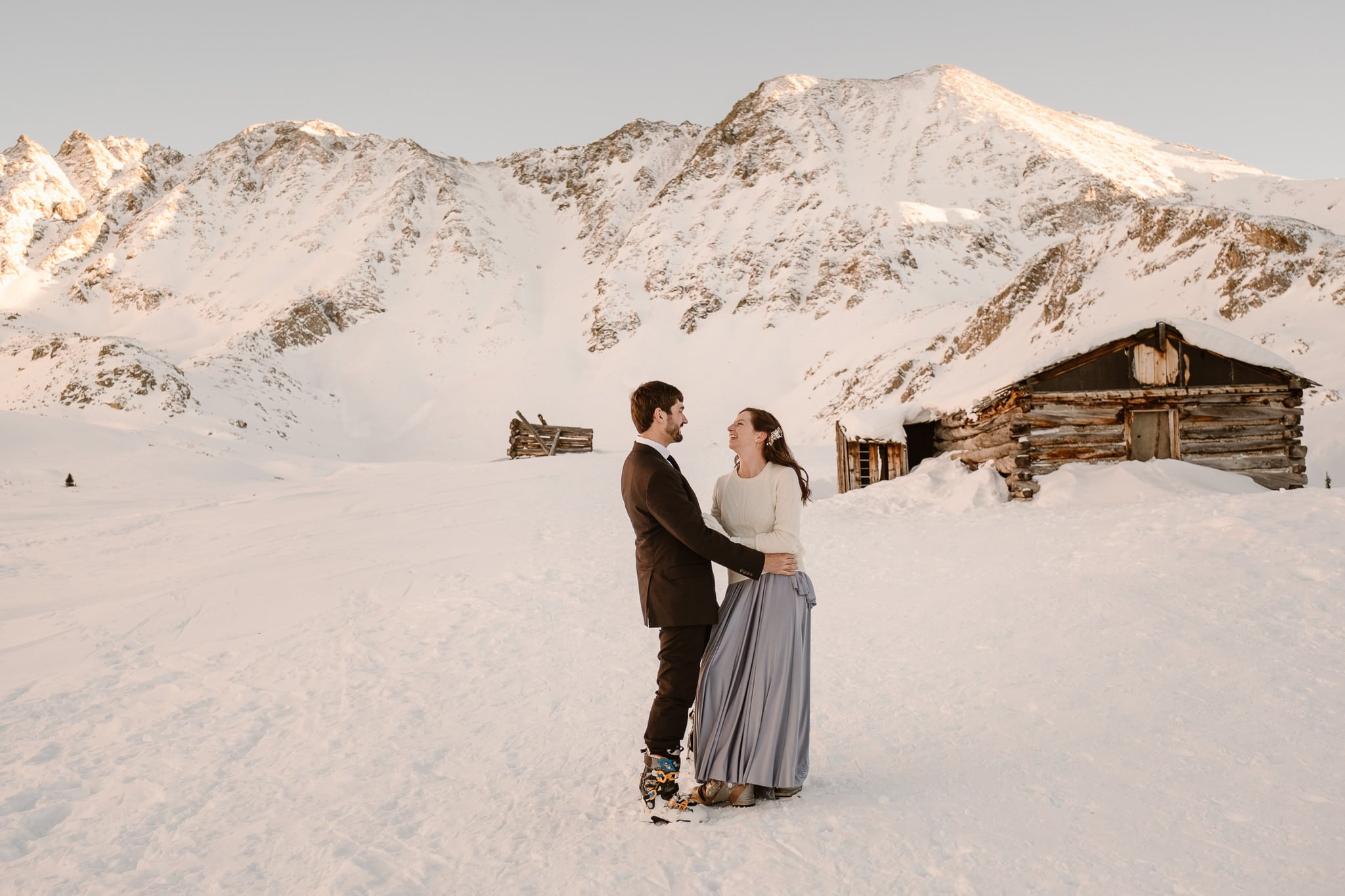 Bride and groom playing at Mayflower Gulch in Colorado, backcountry skiing elopement, snow covered mining cabins