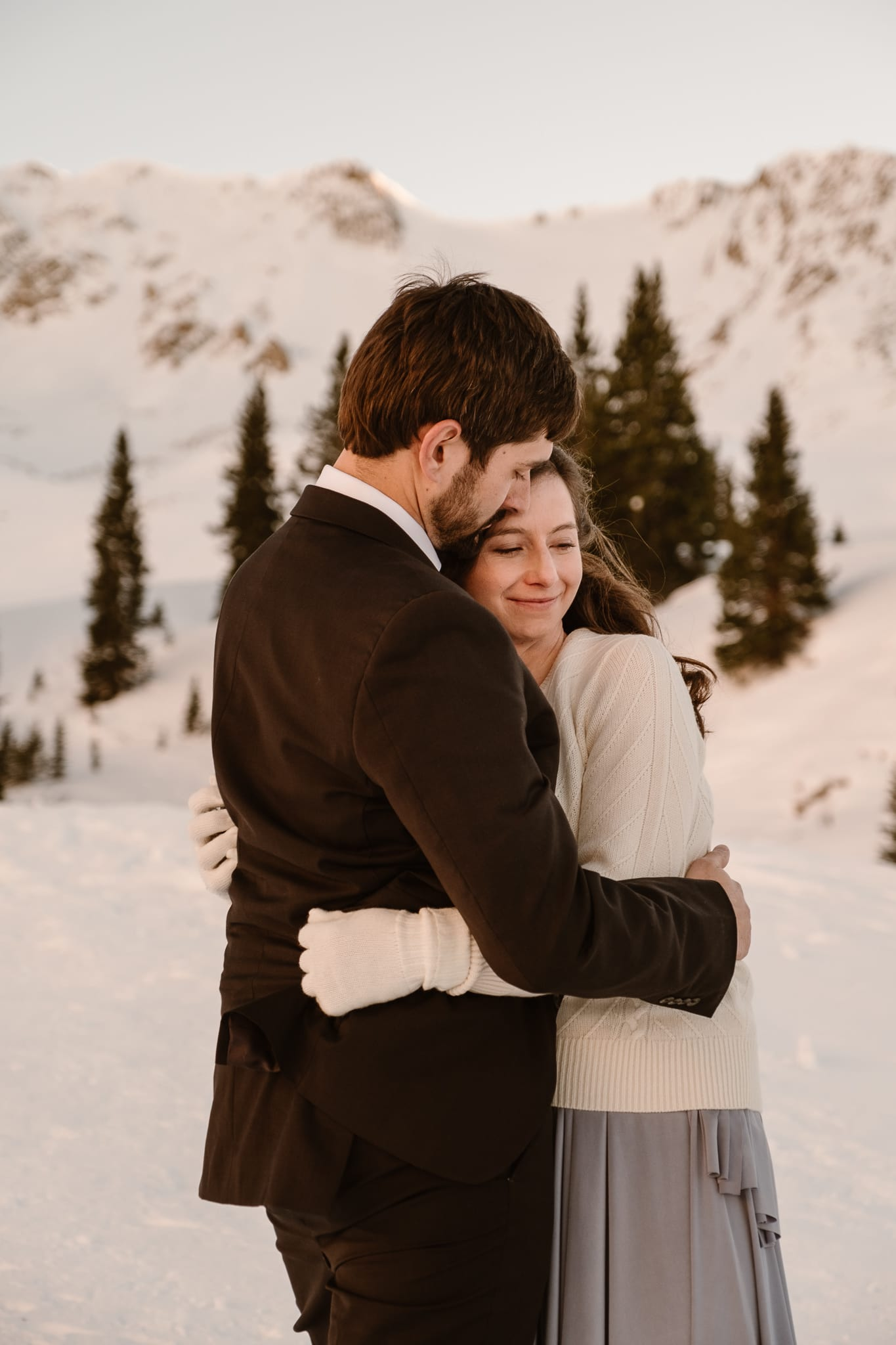 Bride and groom snuggle up close to stay warm at winter wedding, backcountry skiing elopement in Colorado, adventure wedding photographer