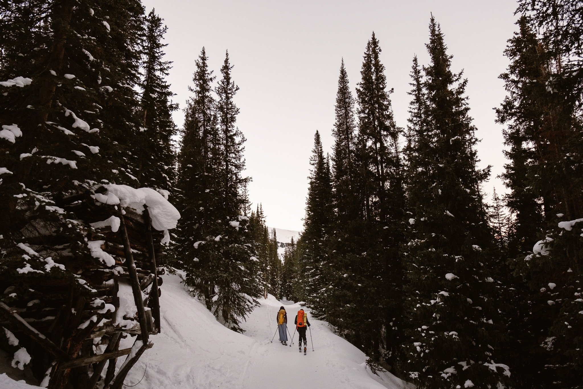 Bride and groom skiing while wearing backpacks, backcountry skiing elopement, Colorado winter wedding, Colorado mountain wedding photographer