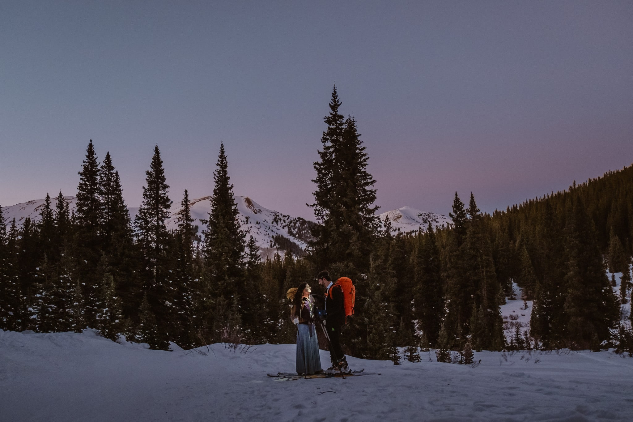 Bride and groom skiing in Colorado mountains at sunset, blue hour wedding photos, Colorado adventure wedding photographer