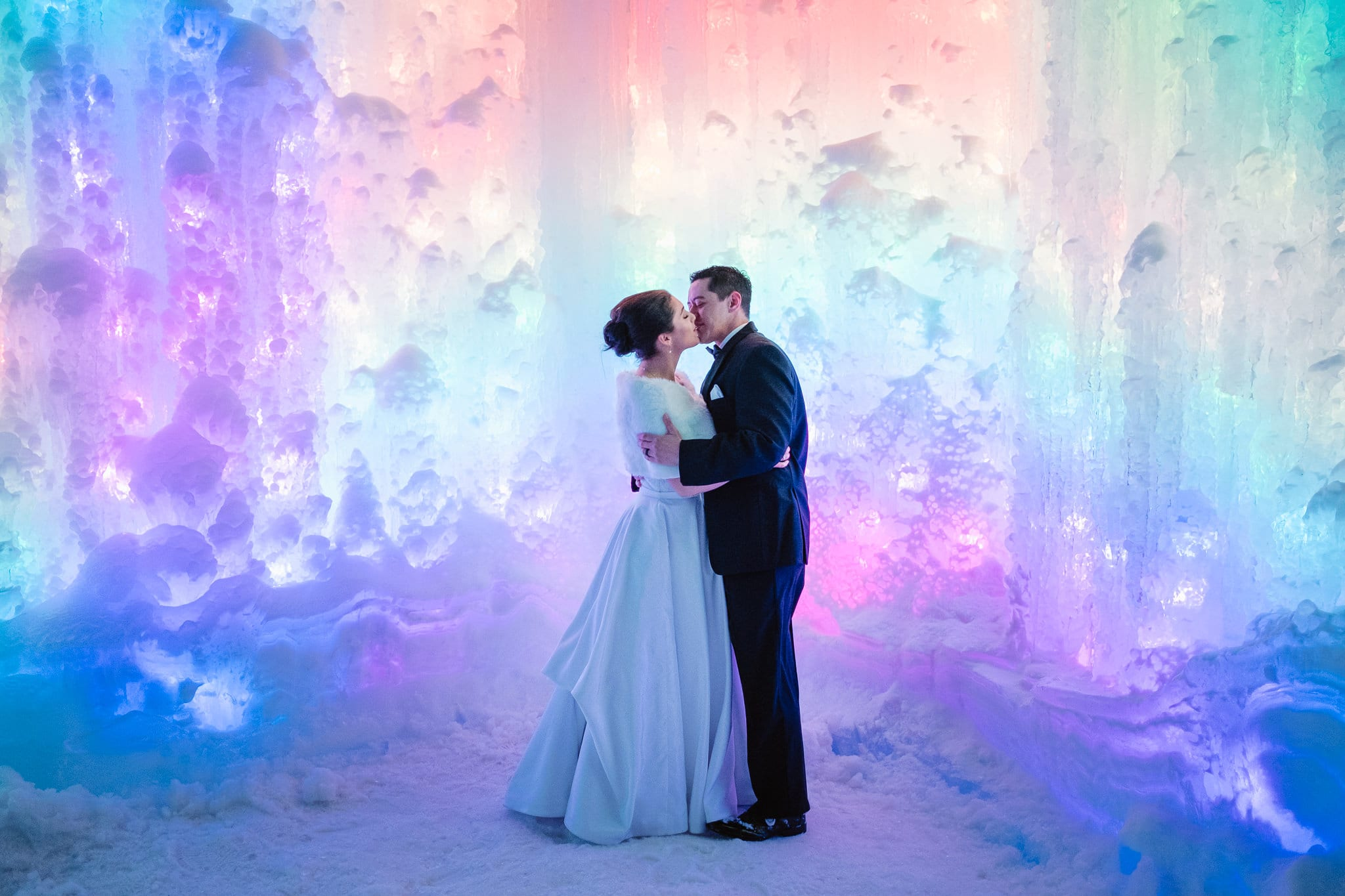 Ice Castles wedding photography, Dillon Colorado winter elopement, bride and groom inside ice castle lit up with rainbow lights