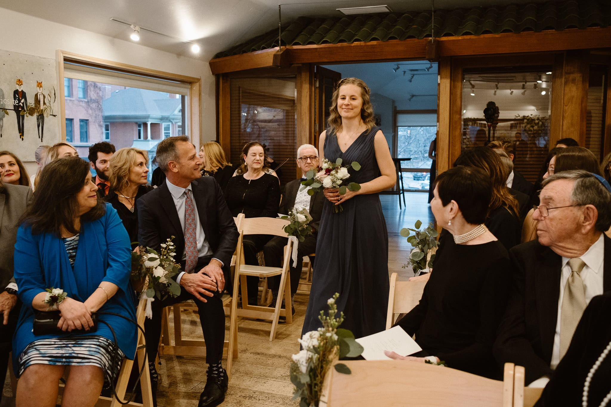 Rembrandt Yard wedding photographer, Boulder wedding photographer, Colorado Jewish wedding, bridesmaid walking down aisle in dark blue dress