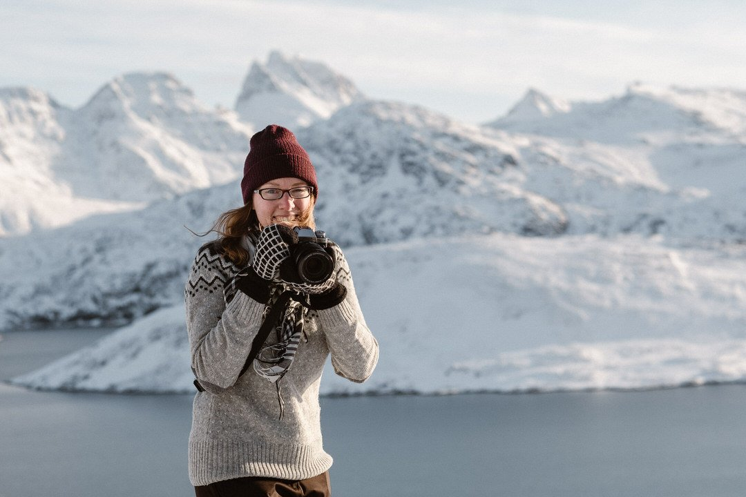 Photographer in front of snow covered mountains