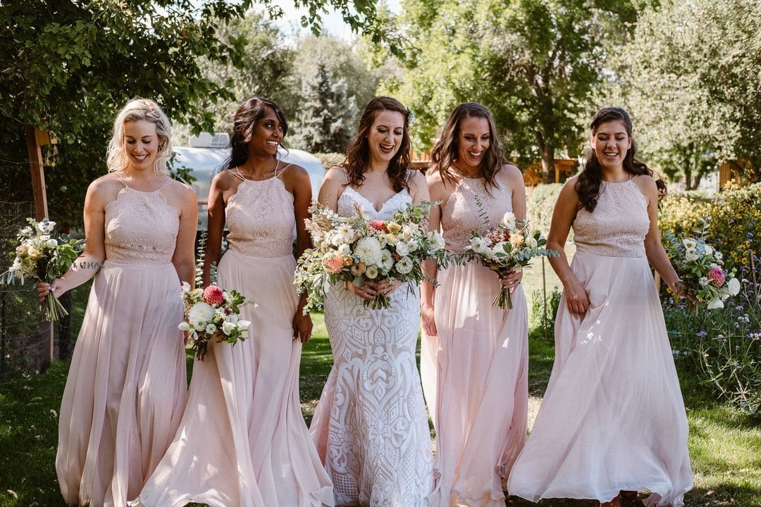 Bride and bridesmaids walking through gardens at Lyons Farmette wedding