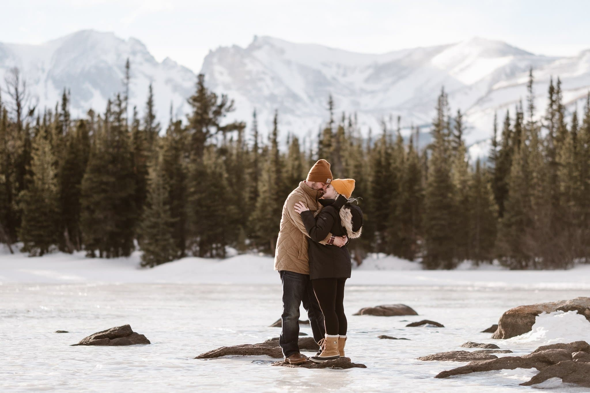 Couple kissing on frozen alpine lake with mountain views behind, Boulder winter engagement session, Colorado adventure wedding photographer