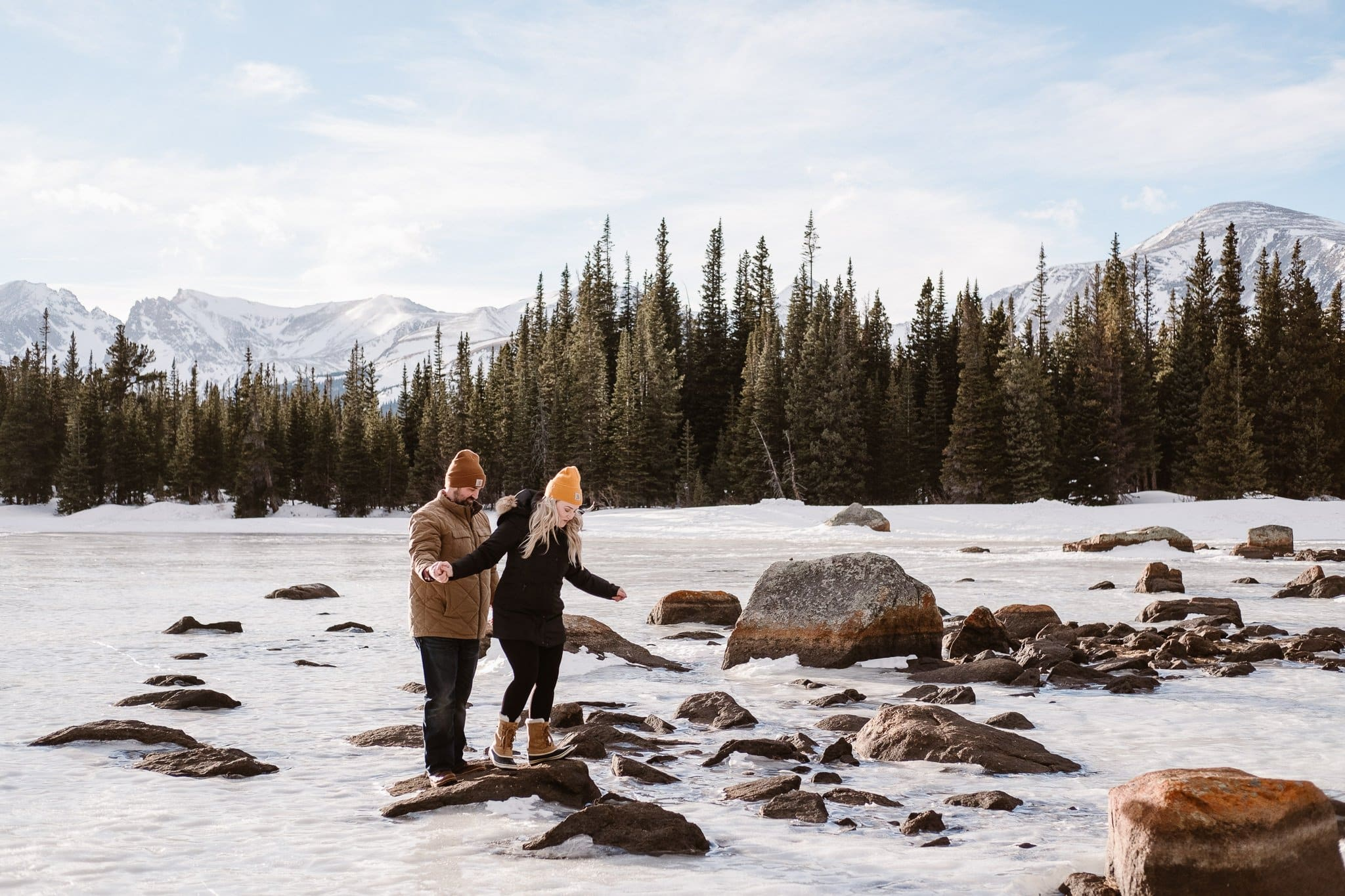 Couple hiking over frozen alpine lake together, Boulder winter engagement session, Colorado adventure session,