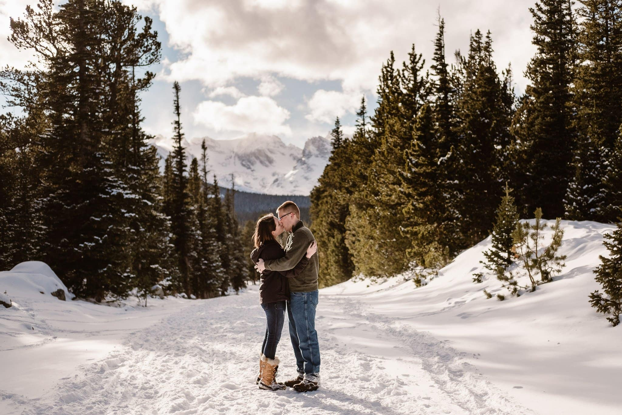 Couple hiking in snow covered mountains, Colorado winter engagement session in Indian Peaks Wilderness, Colorado engagement photographer