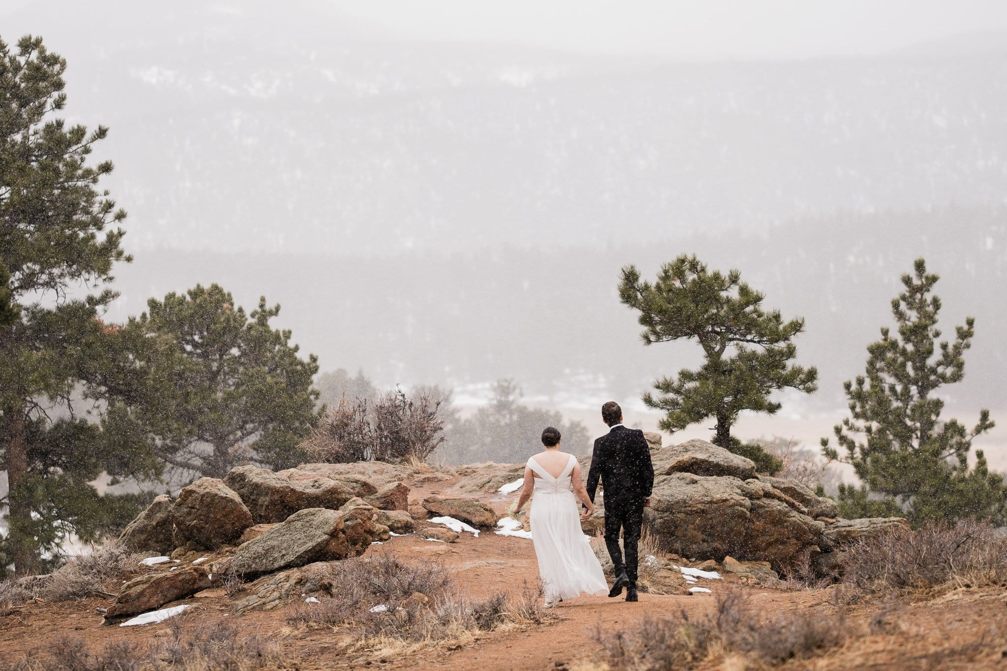 Bride and groom walking in mountains, 3M Curve elopement, winter wedding in Rocky Mountain National Park
