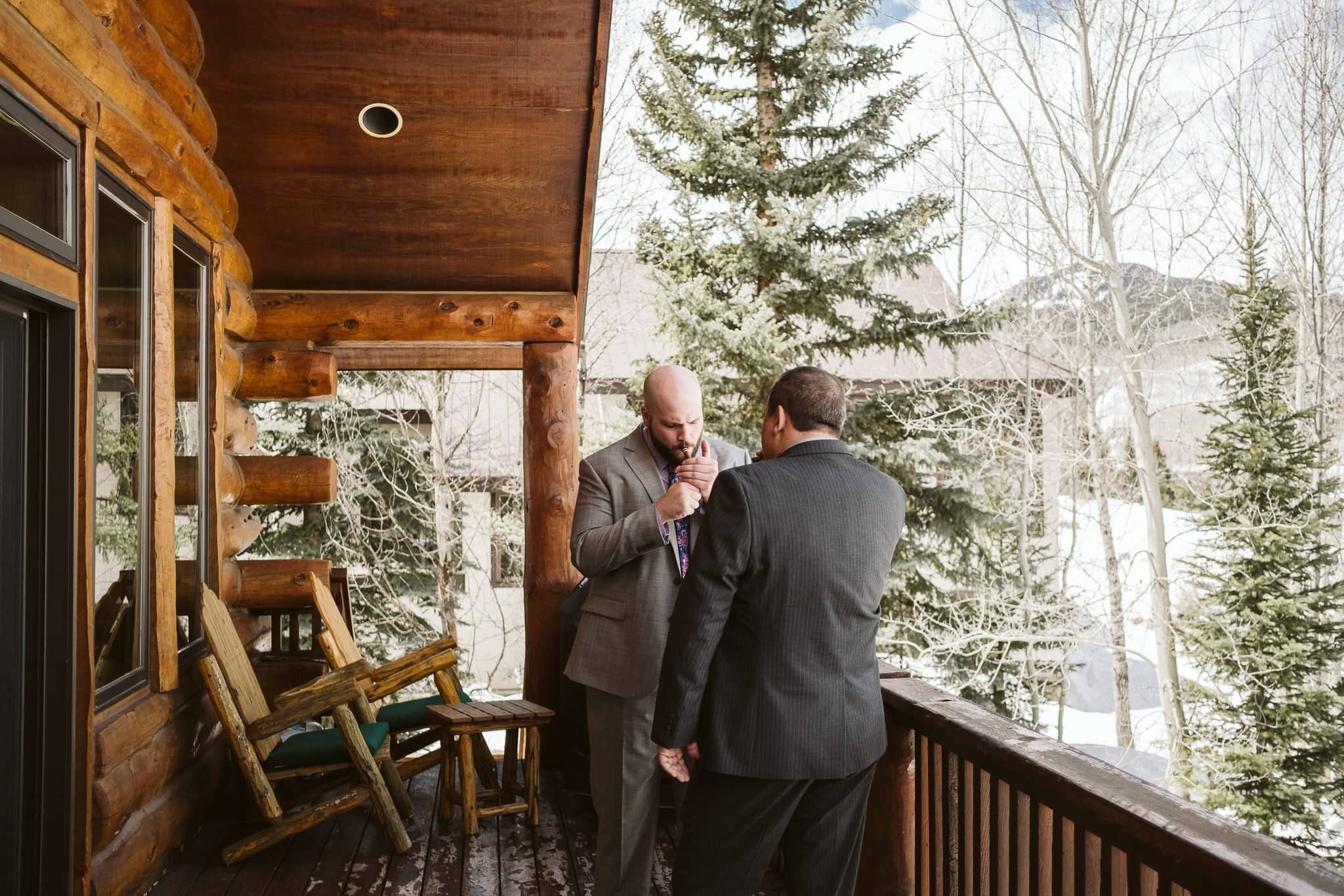 Groom and father of the bride smoking cigar on deck of log cabin