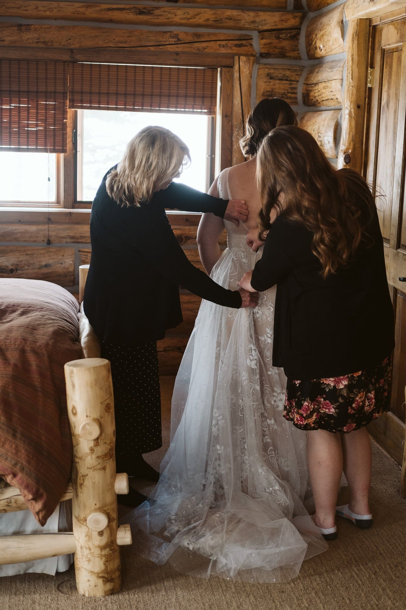 Bride's mother and sister helping her into wedding dress