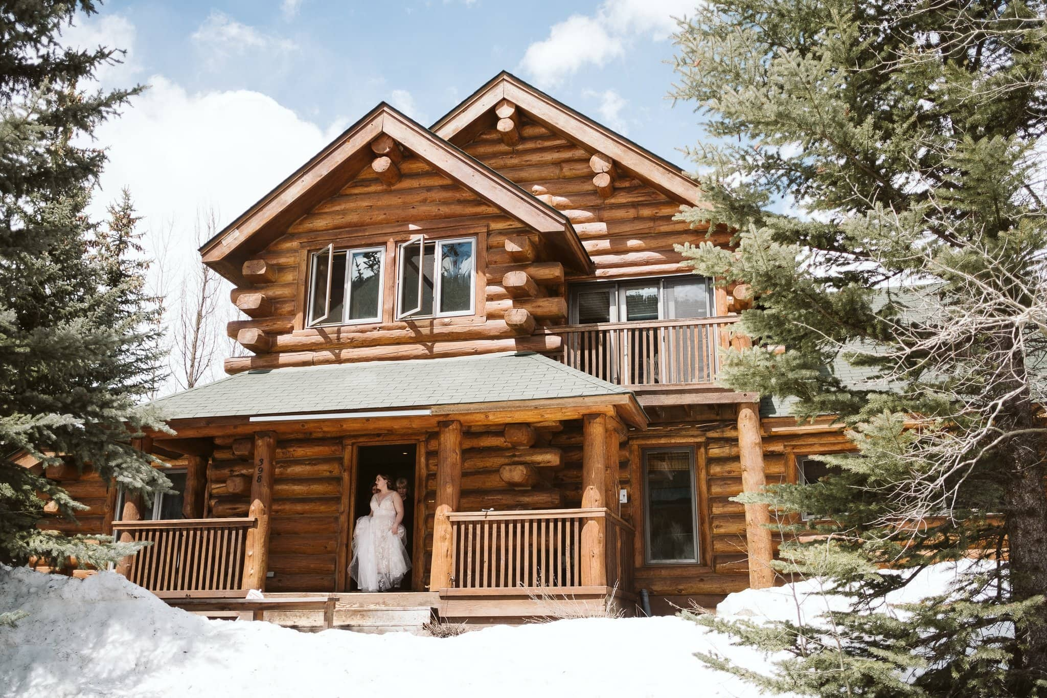 Bride walking out of log cabin home in Crested Butte for winter elopement
