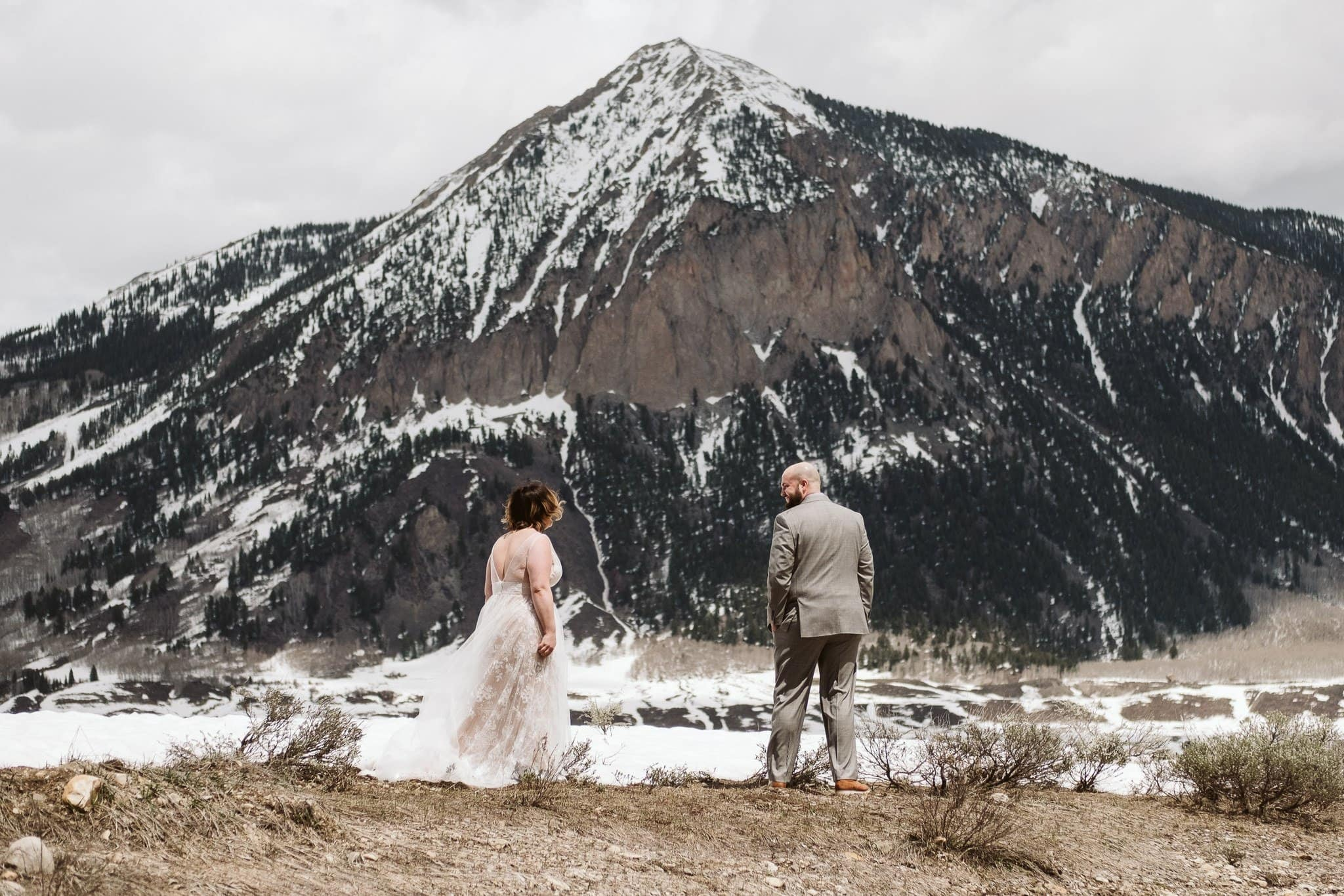 Bride and groom first look with Mount Crested Butte in the background, winter elopement in Colorado