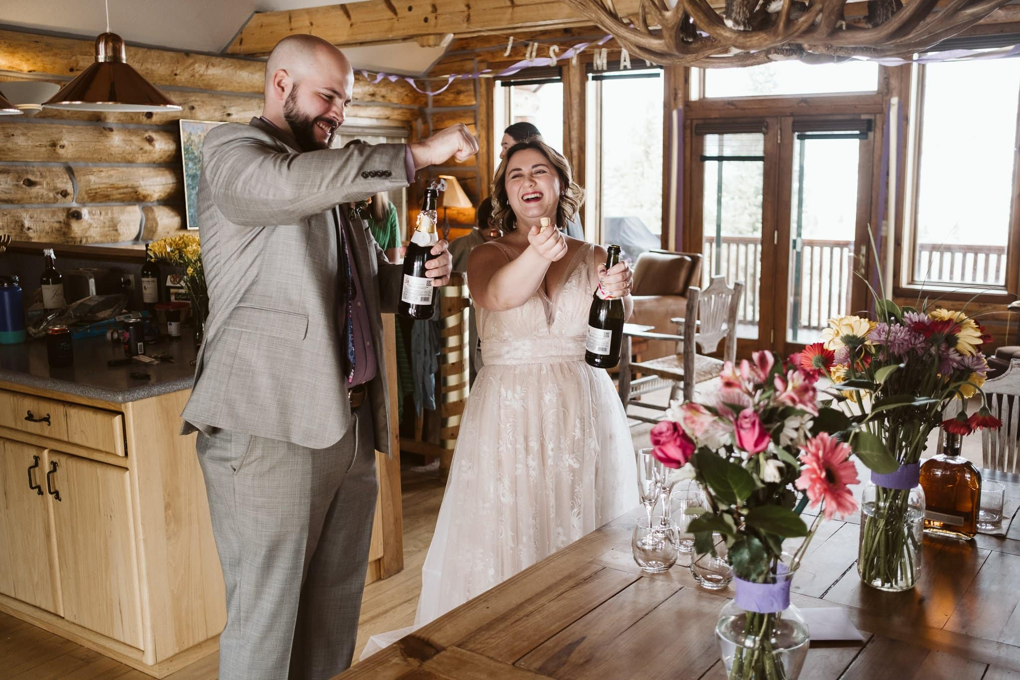 Bride and groom popping bottles of champagne for toasts