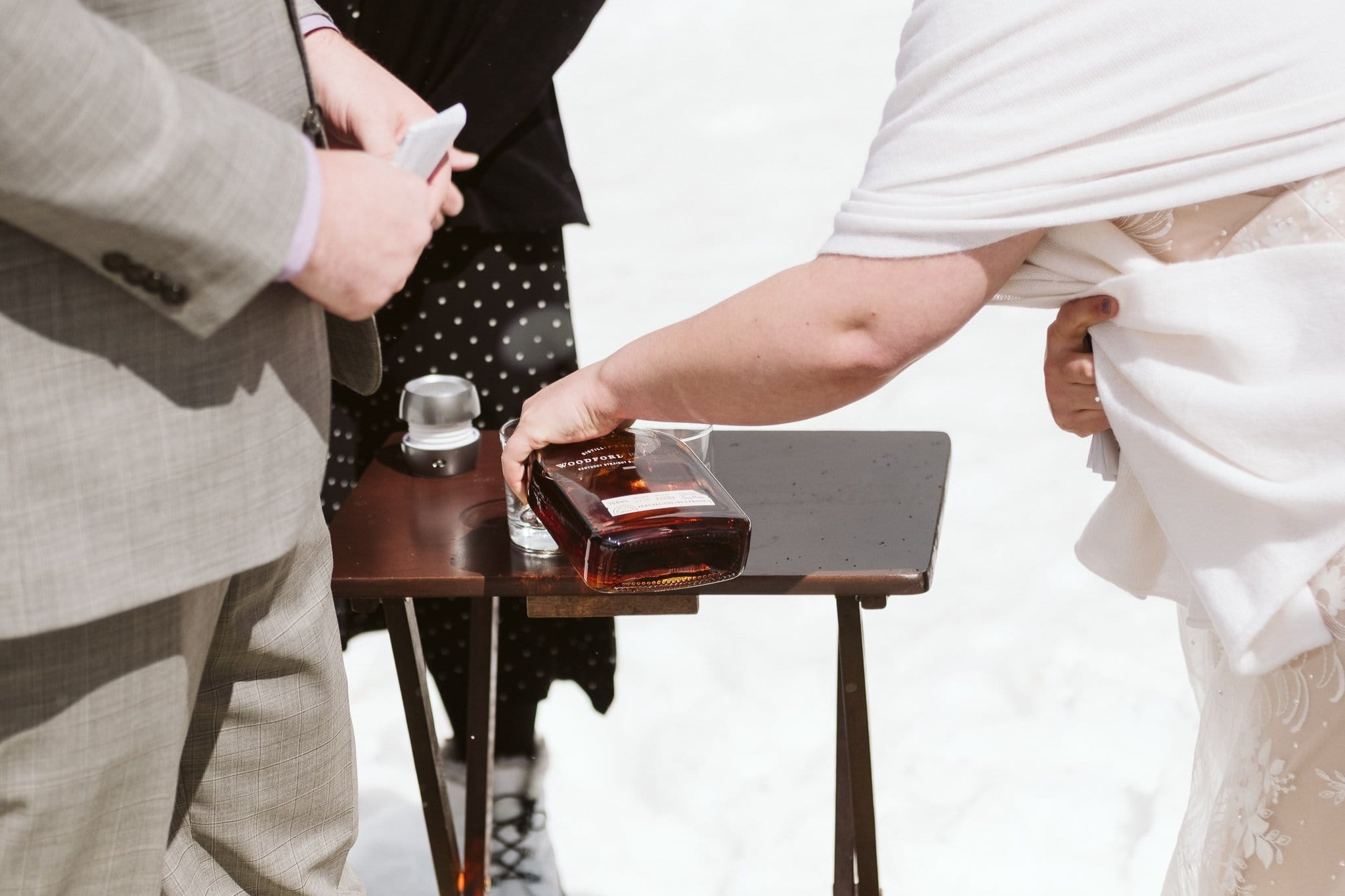 Bride pouring whiskey as part of elopement ceremony