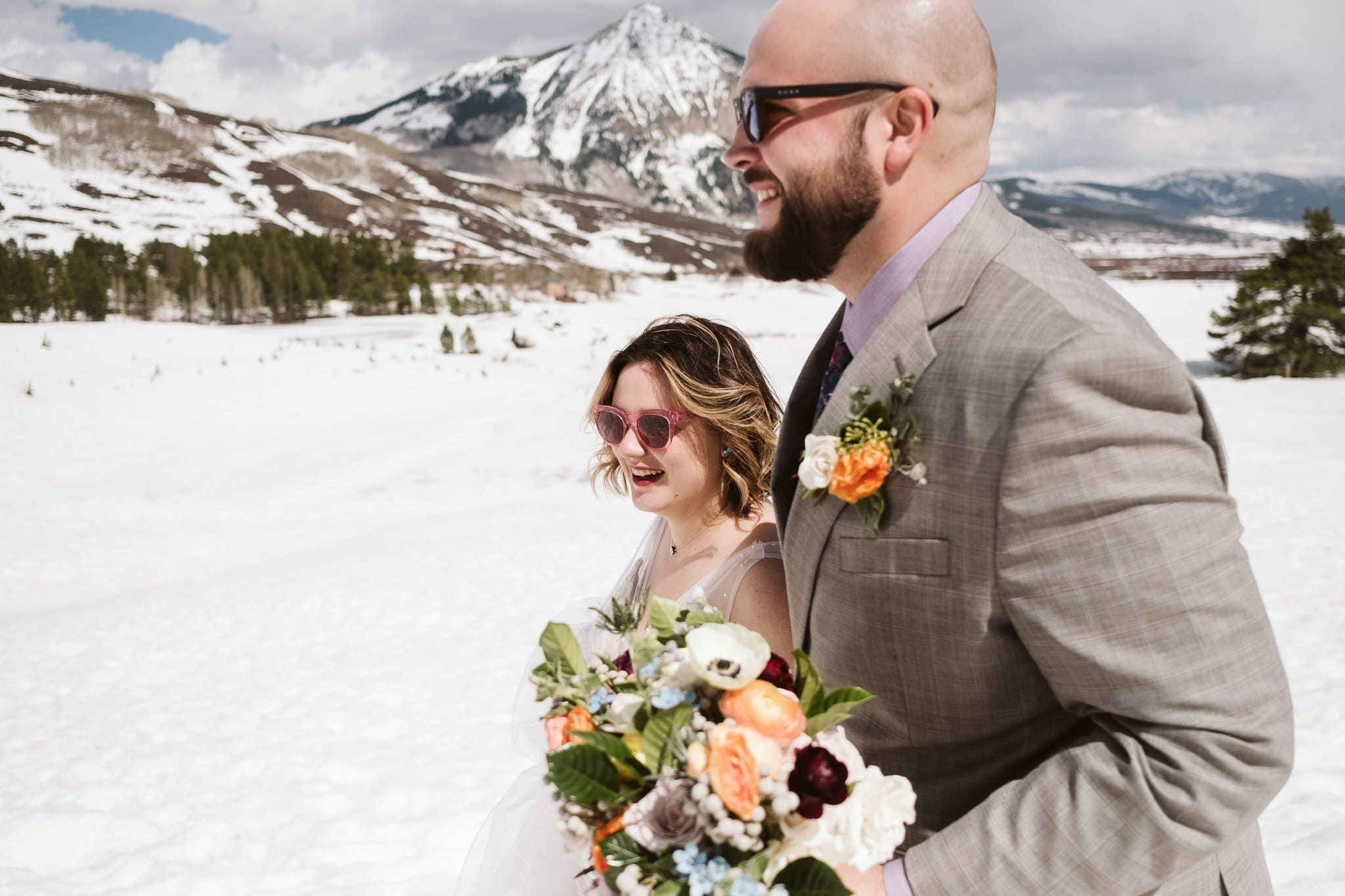 Bride and groom hiking in snow wearing sunglasses, Crested Butte elopement in winter