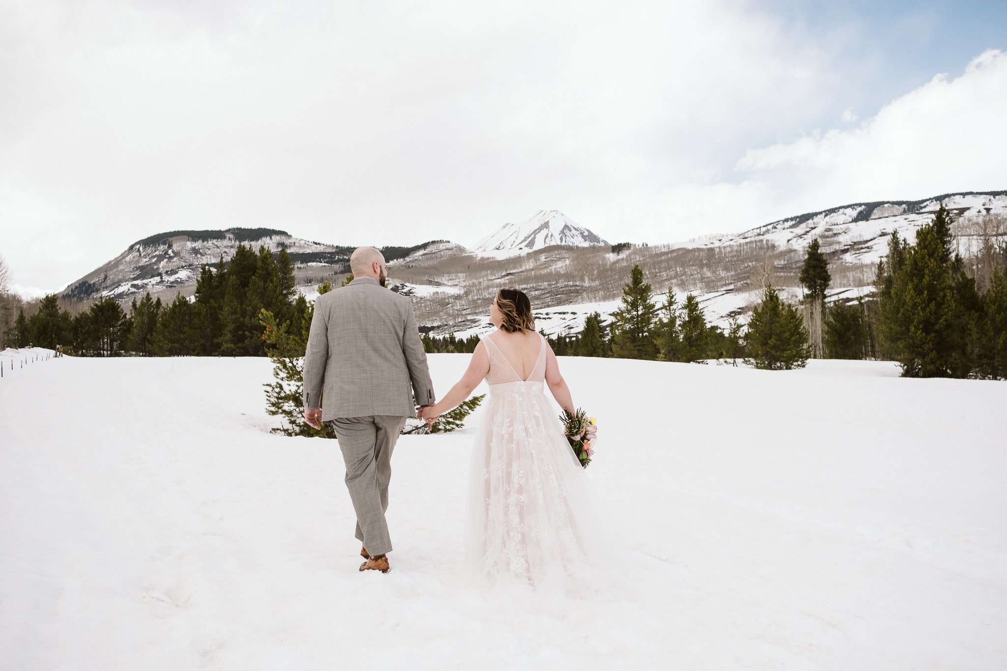 Bride and groom walking in snowy landscape in Crested Butte
