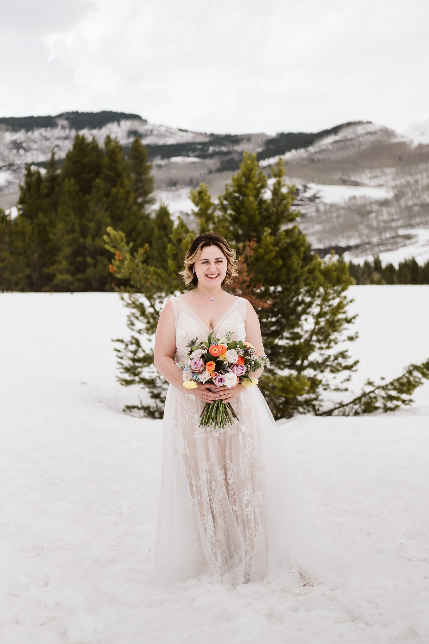 Bride holding Spring colored wedding bouquet by From the Ground Up Flowers in Crested Butte, blush wedding dress in snow, bridal portrait