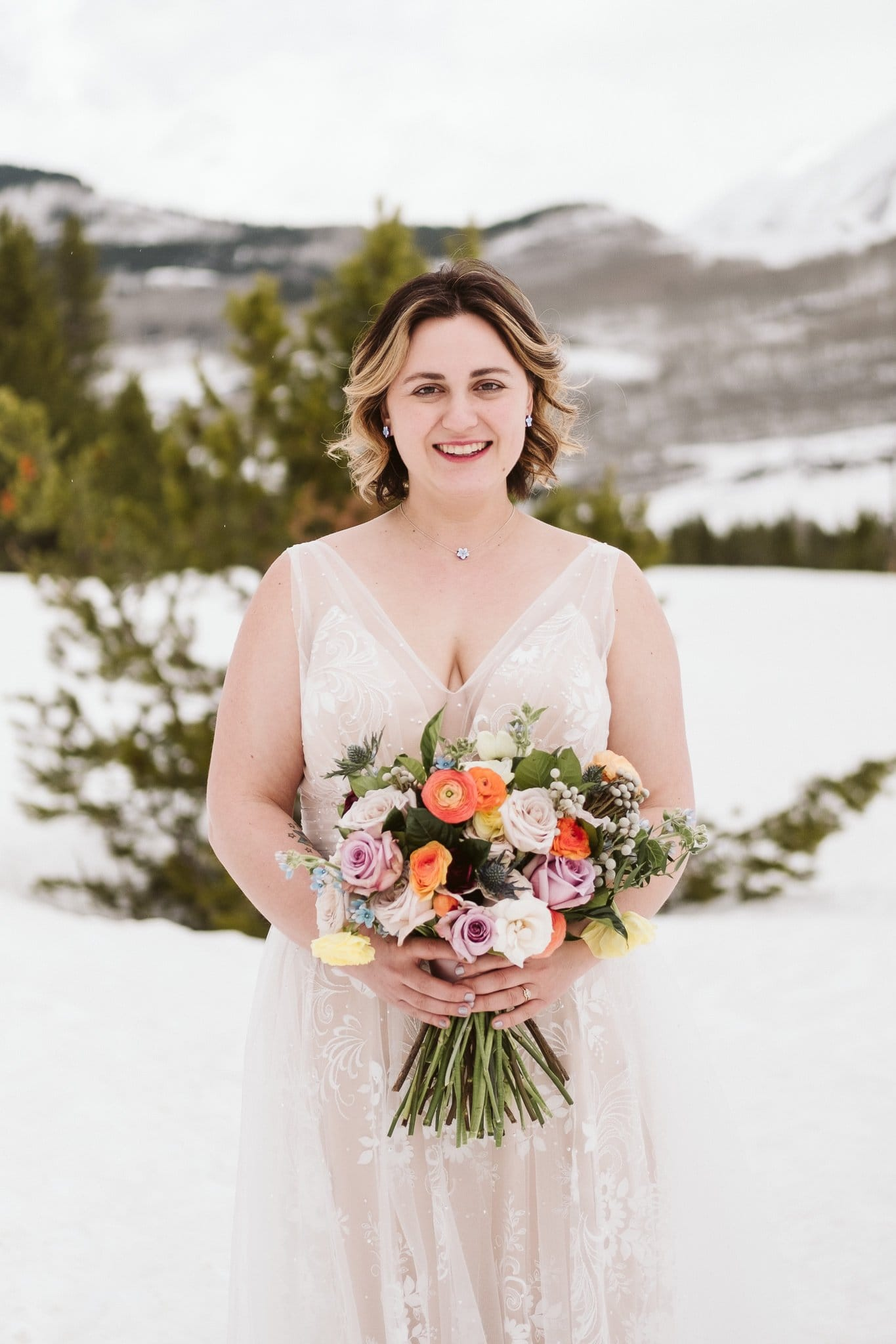 Bride holding Spring colored wedding bouquet by From the Ground Up Flowers in Crested Butte, blush wedding dress in snow