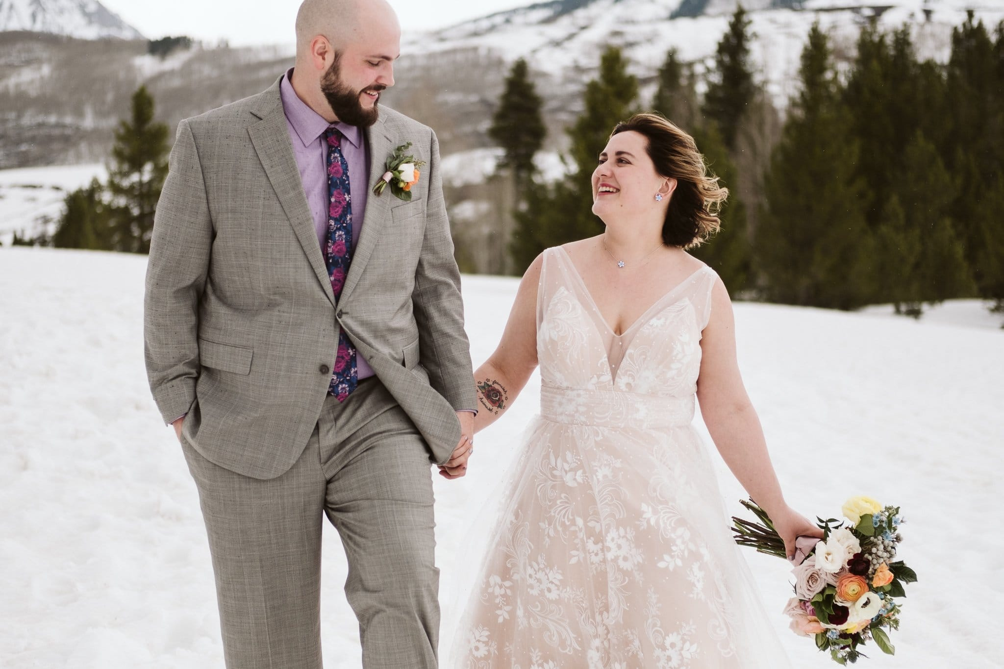 Bride and groom hiking in snowy landscape, winter elopement in the Colorado mountains