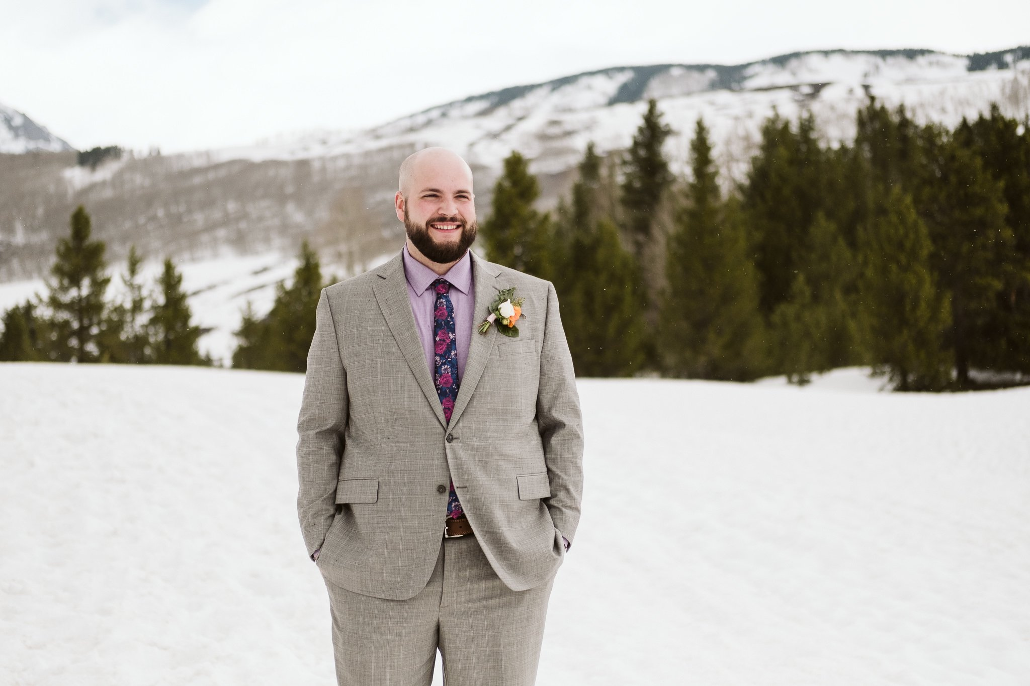 Groom wearing grey suit and purple shirt and tie for winter wedding