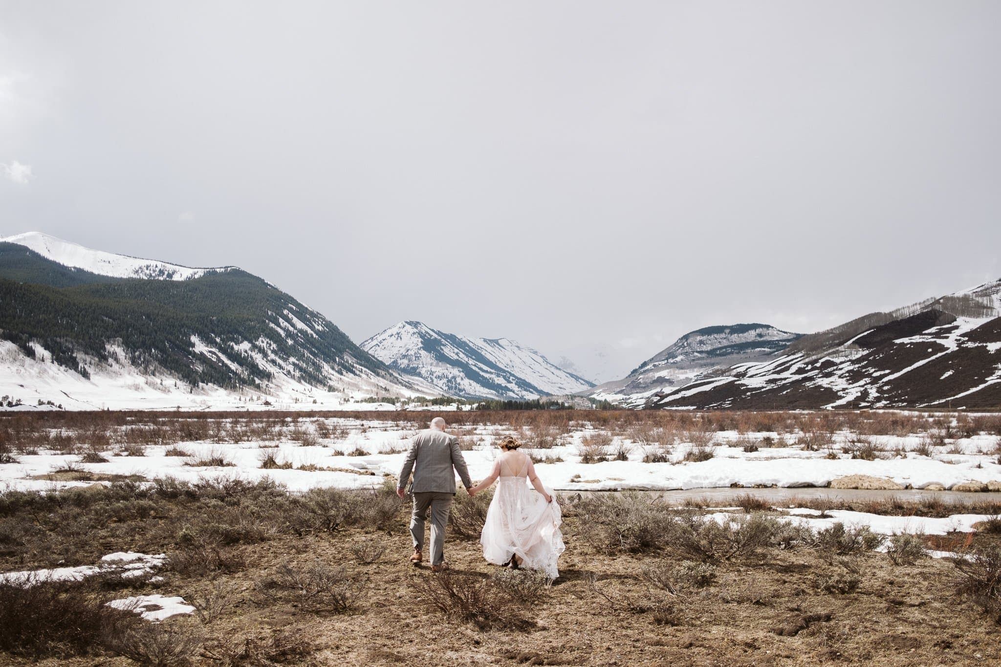 Bride and groom hiking through snow-covered valley, Crested Butte winter elopement photography