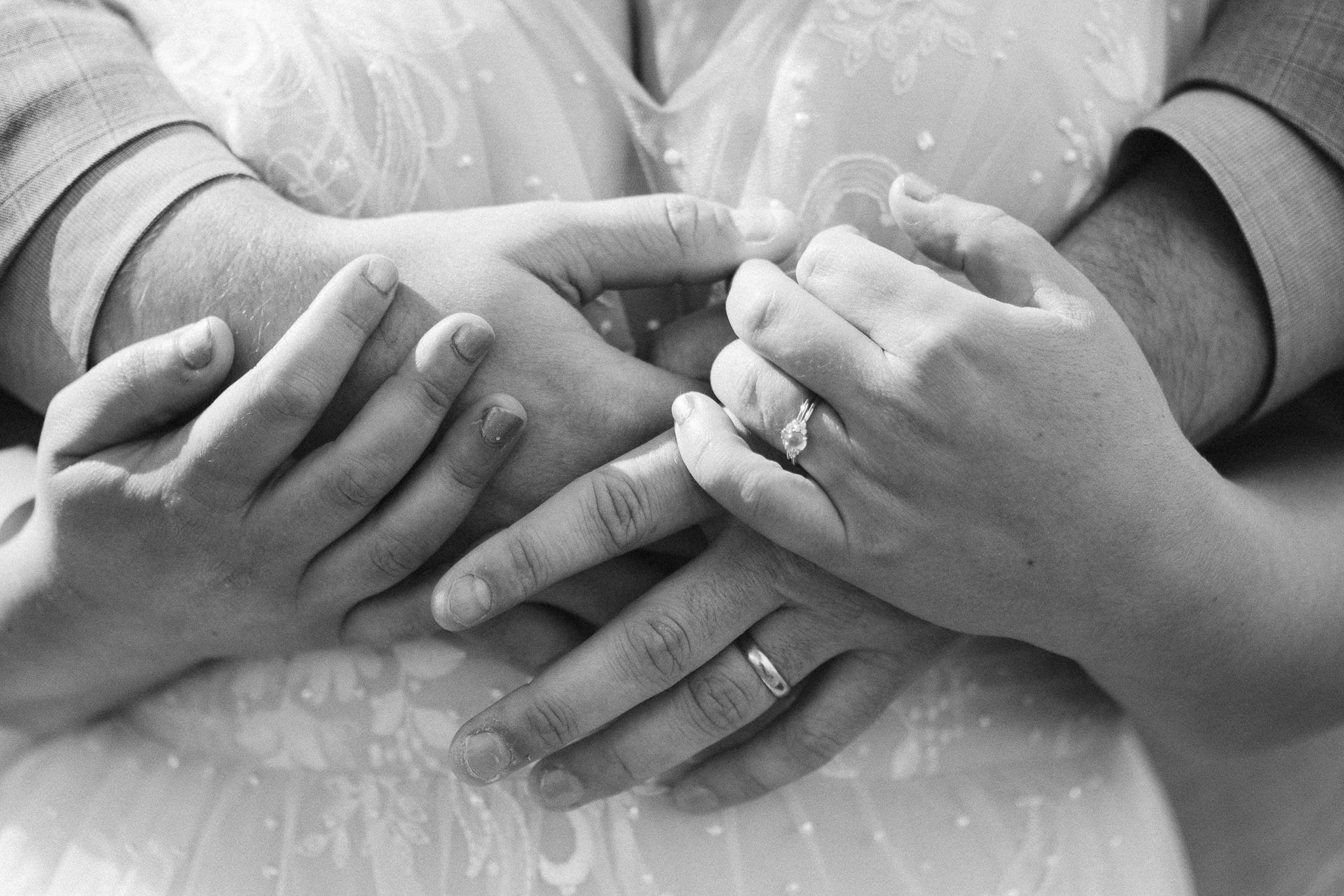 Close up of bride and groom's hands with wedding rings
