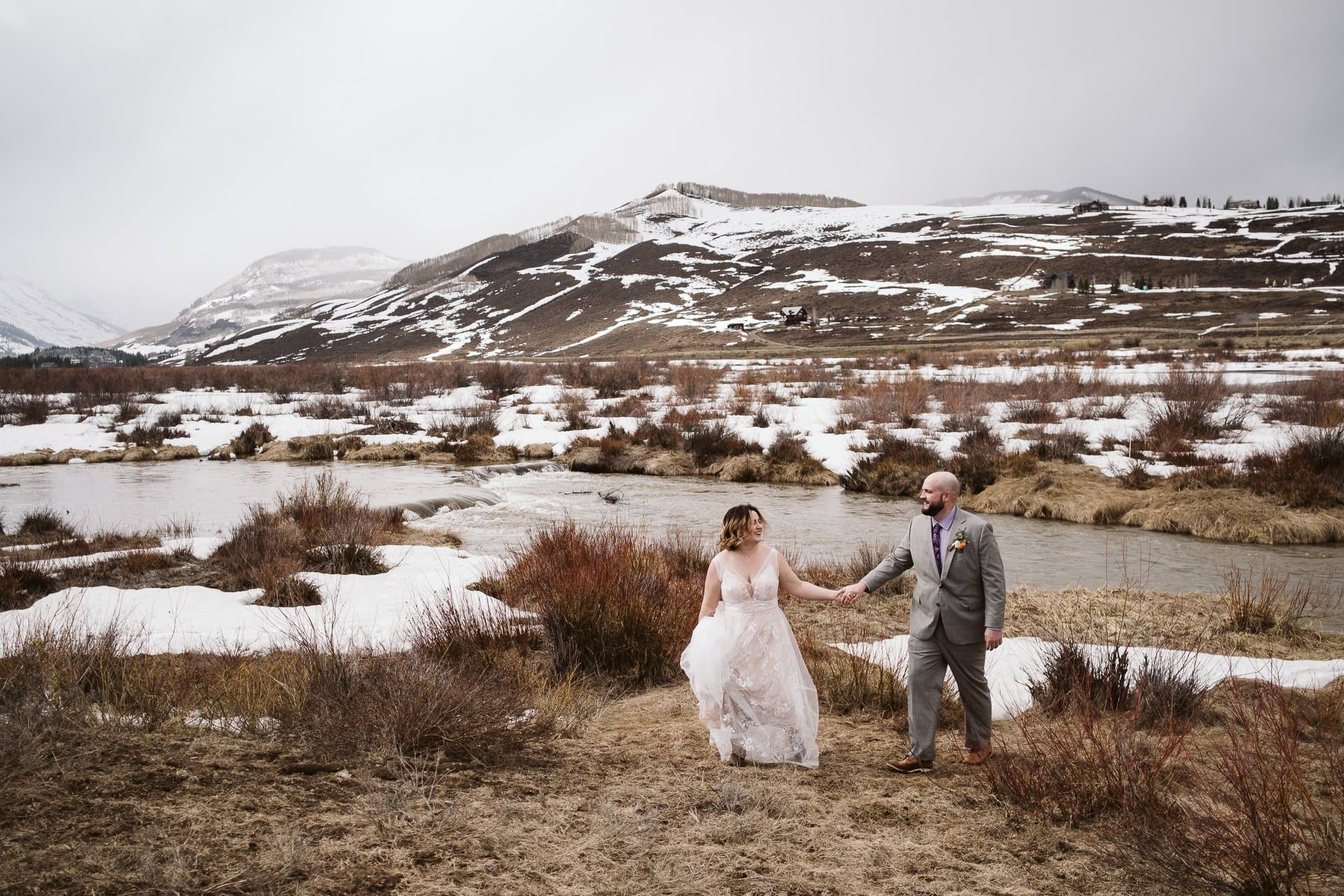 Bride and groom walking along river in winter