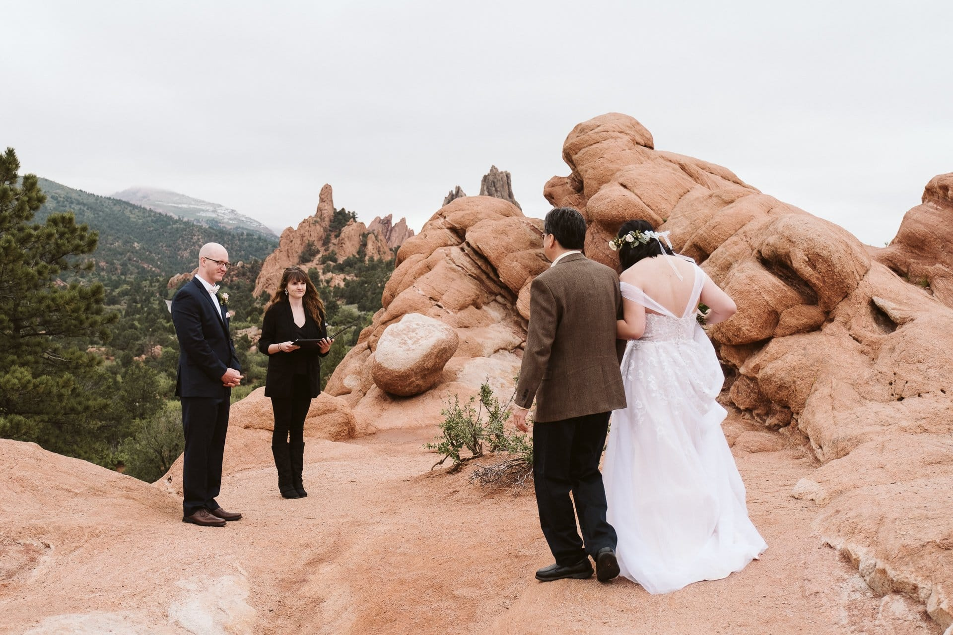 Father walking bride down the trail at adventure elopement at Garden of the Gods in Colorado Springs