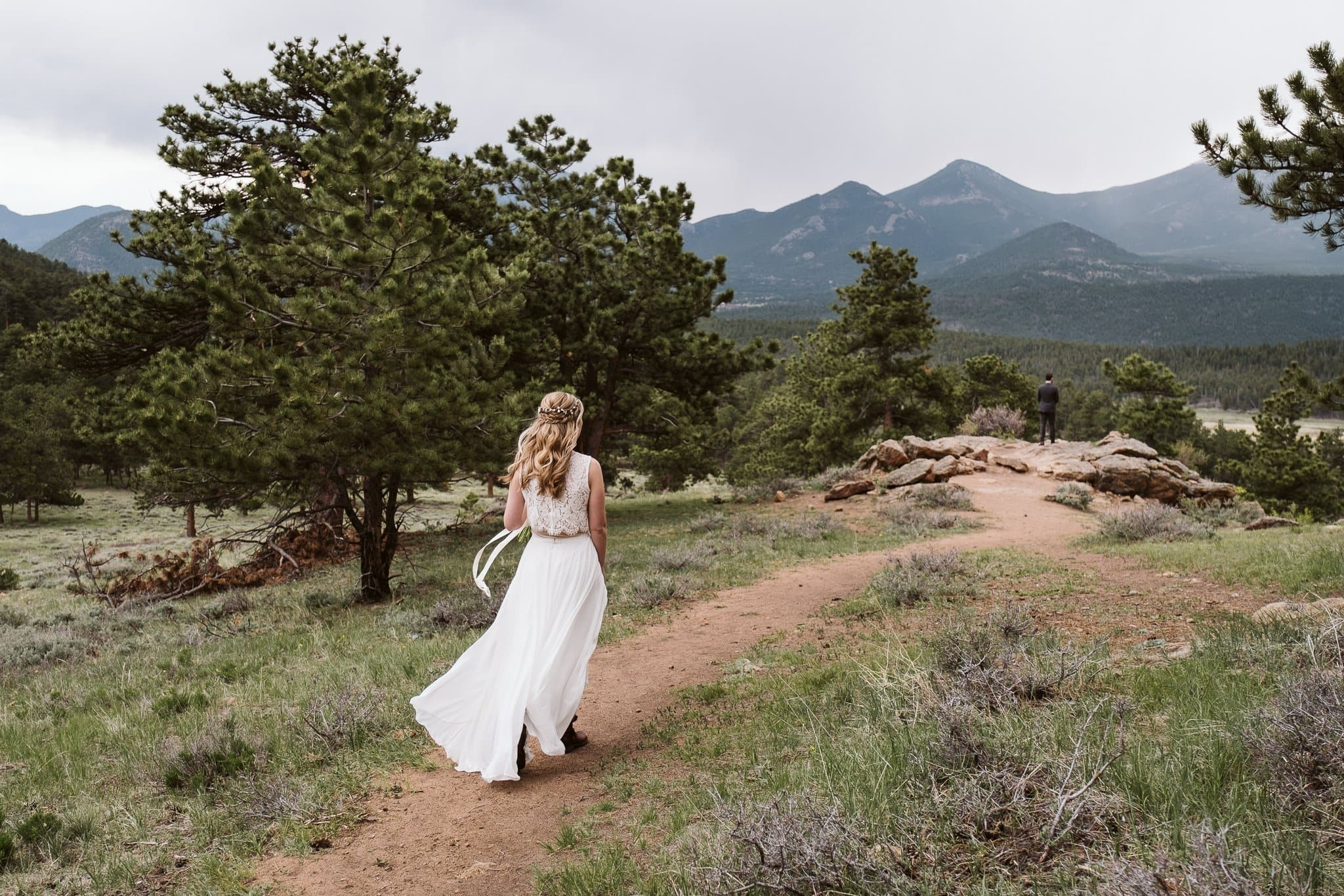 Bride walking towards groom for first look at 3M Curve in Rocky Mountain National Park