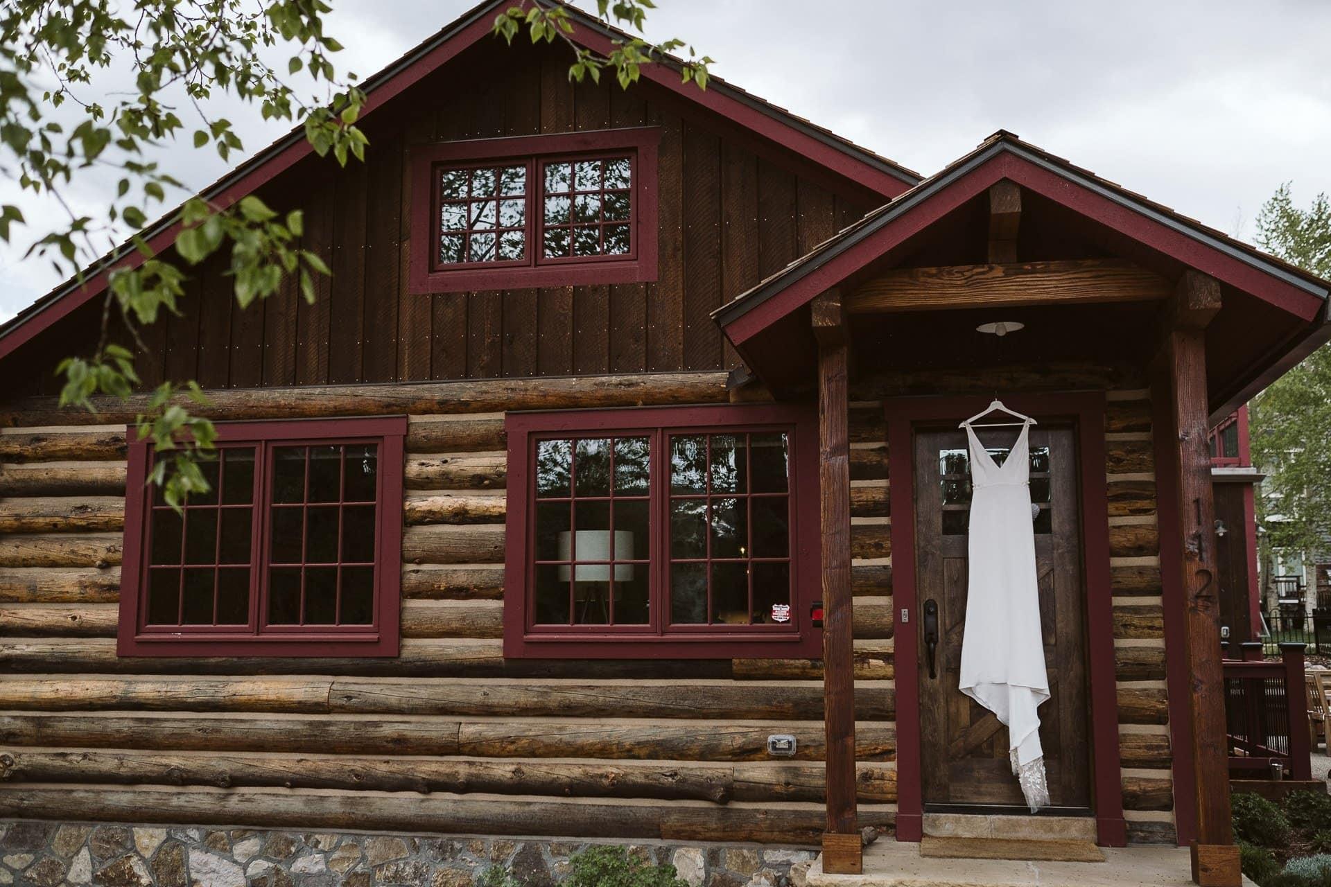 Wedding dress hanging on door of log cabin