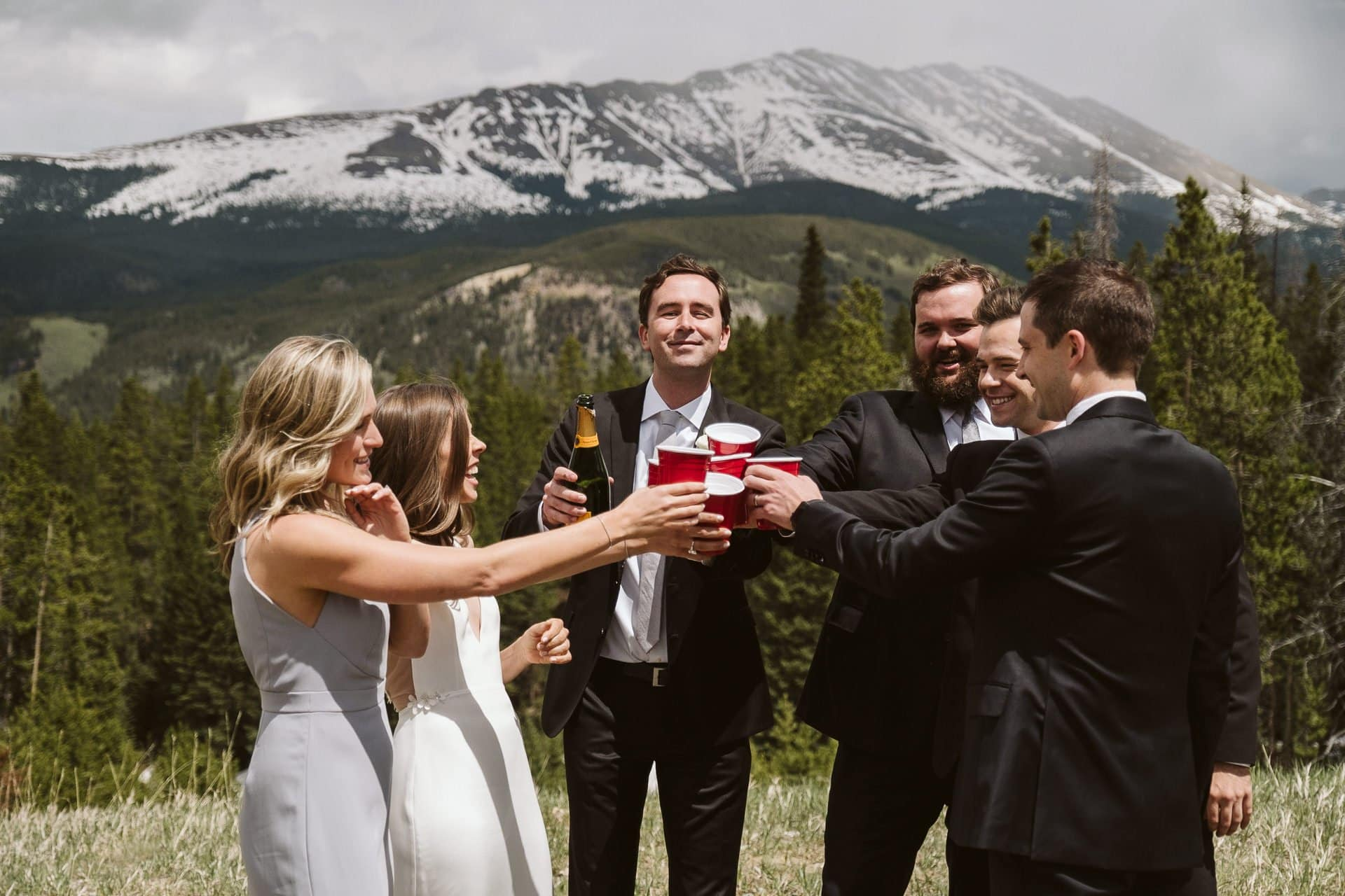 Bride and groom popping champagne with wedding party at Ten Mile Station, Breckenridge ski resort wedding, Colorado mountain wedding photographer