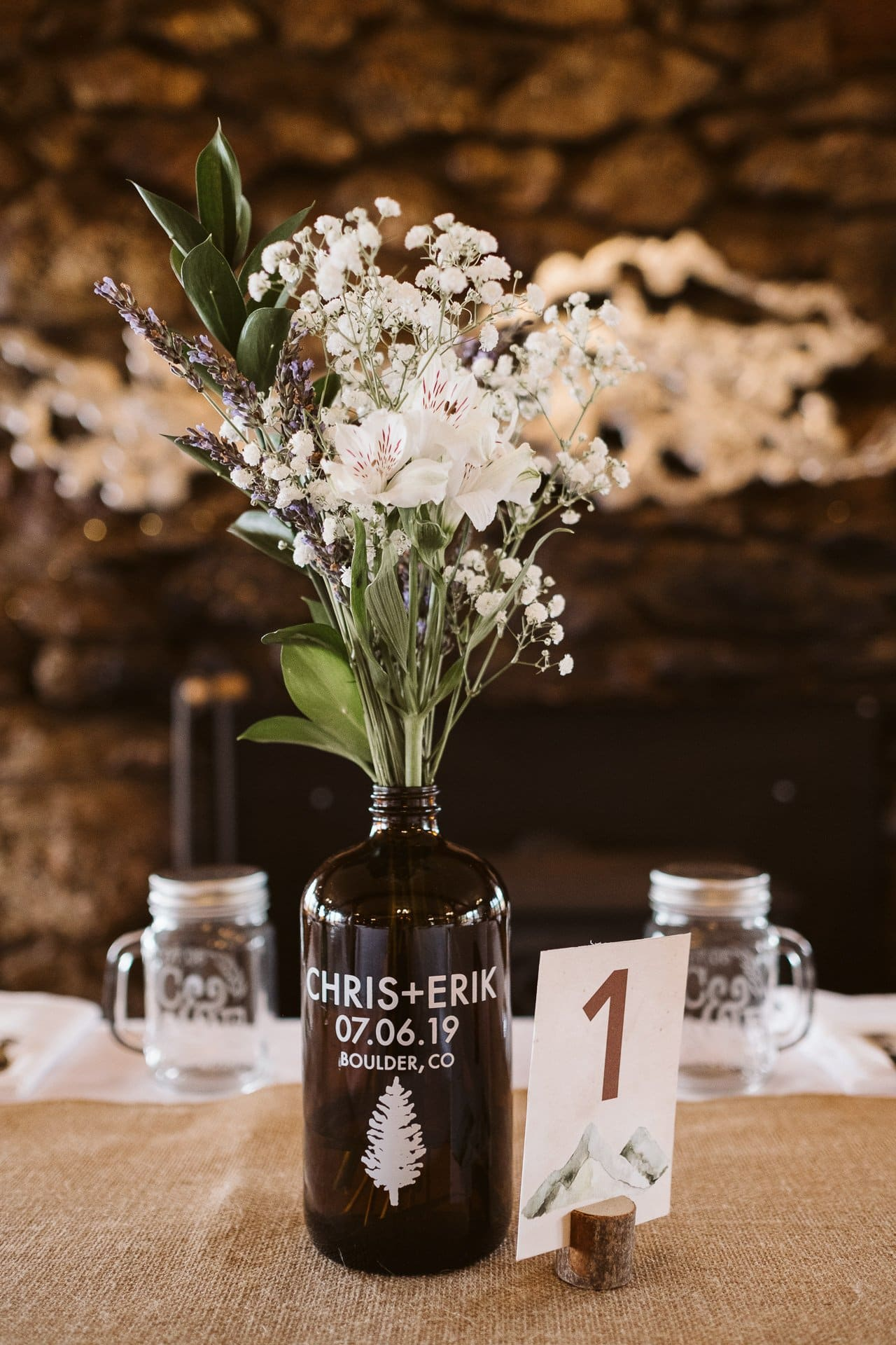 Rustic wood wedding venue at Colorado Mountain Ranch in Boulder, custom printed growlers as centerpieces