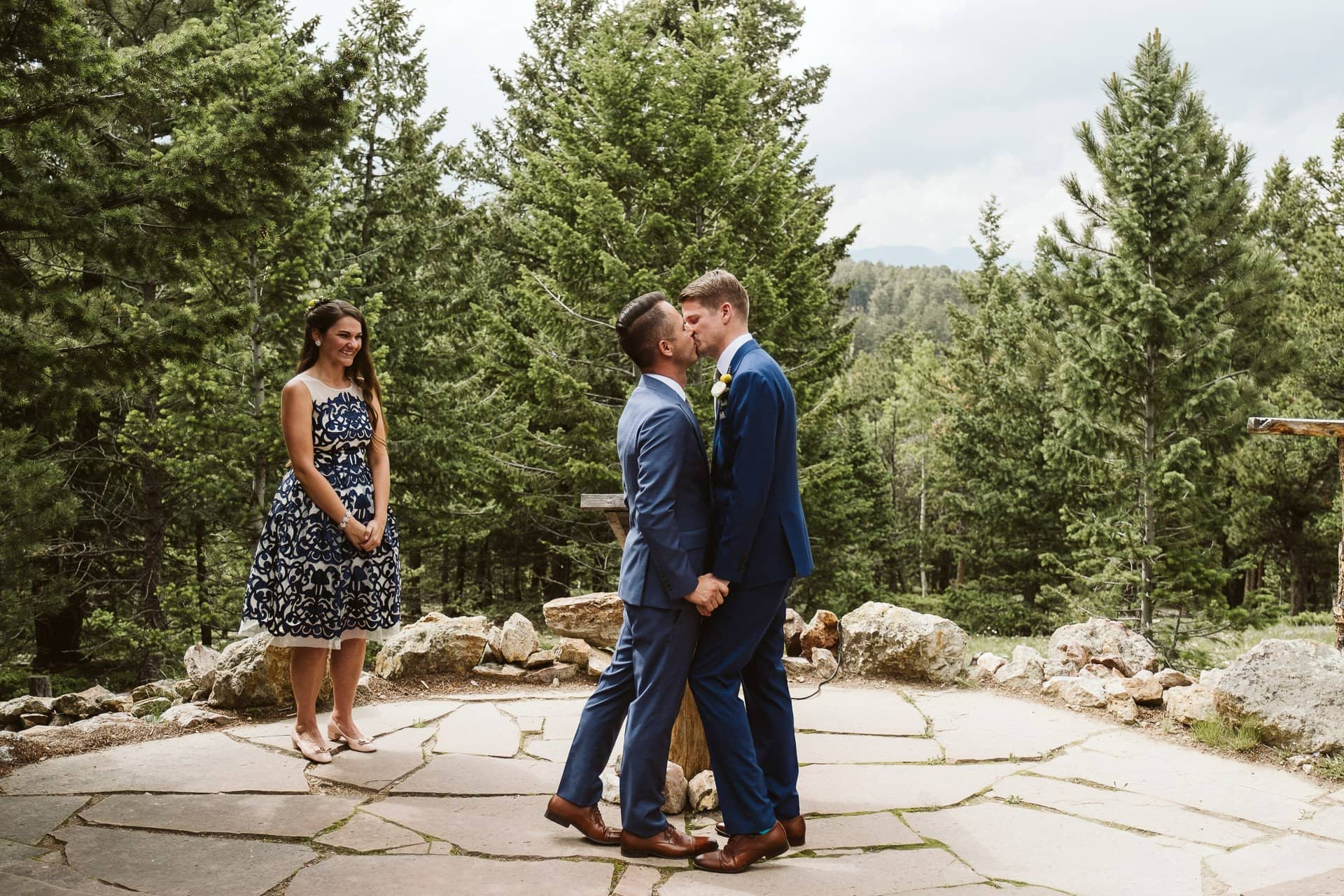 Grooms first kiss in wedding ceremony at Colorado Mountain Ranch outside Boulder, gay wedding in Colorado