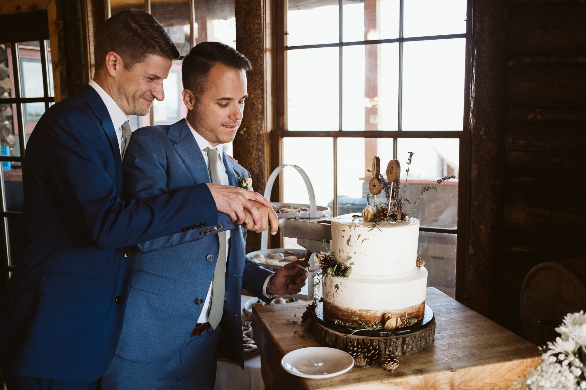Grooms cutting the cake at Colorado Mountain Ranch wedding outside of Boulder, cake by Shamane's Bake Shoppe