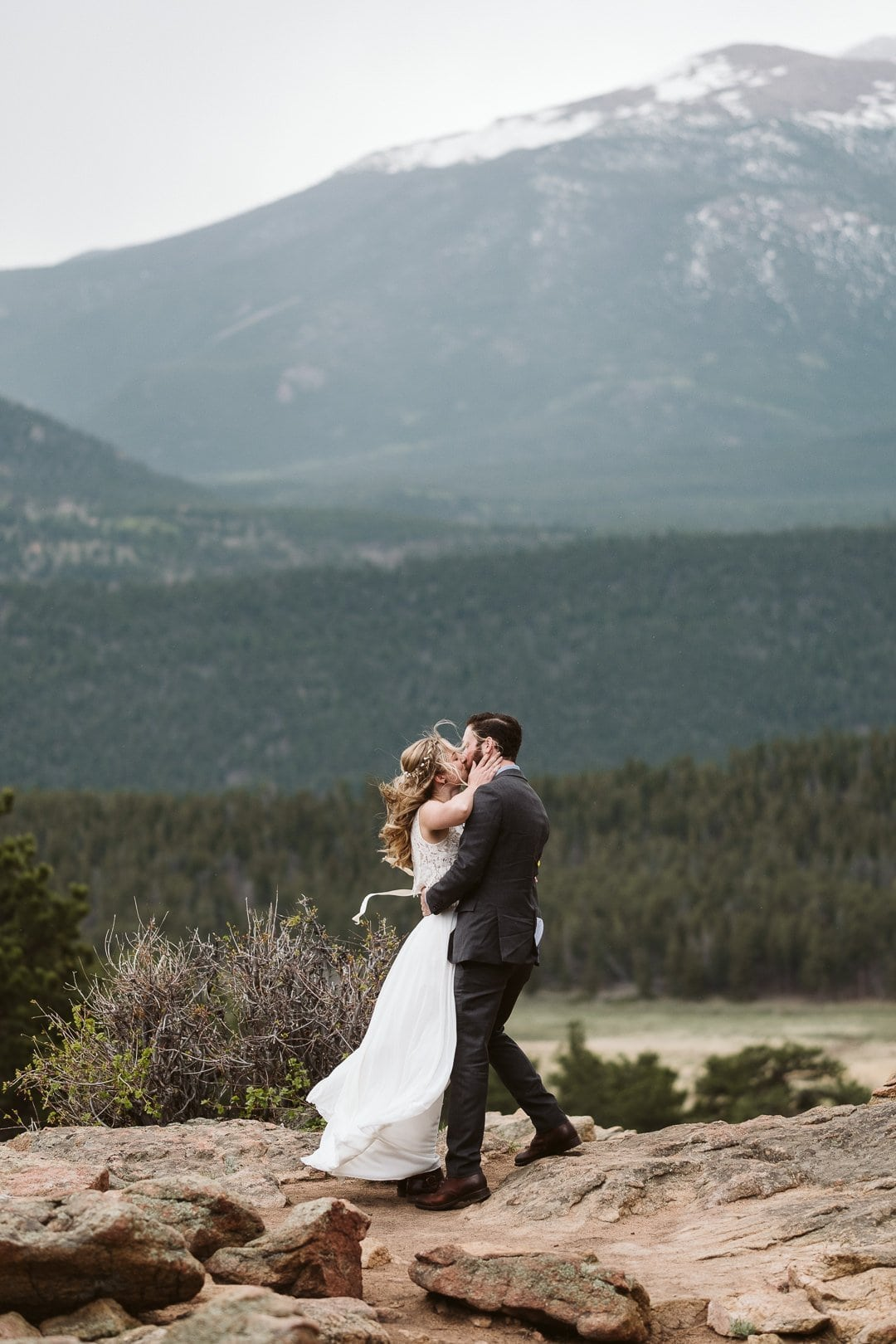 Bride and groom kiss at 3M Curve overlook in RMNP