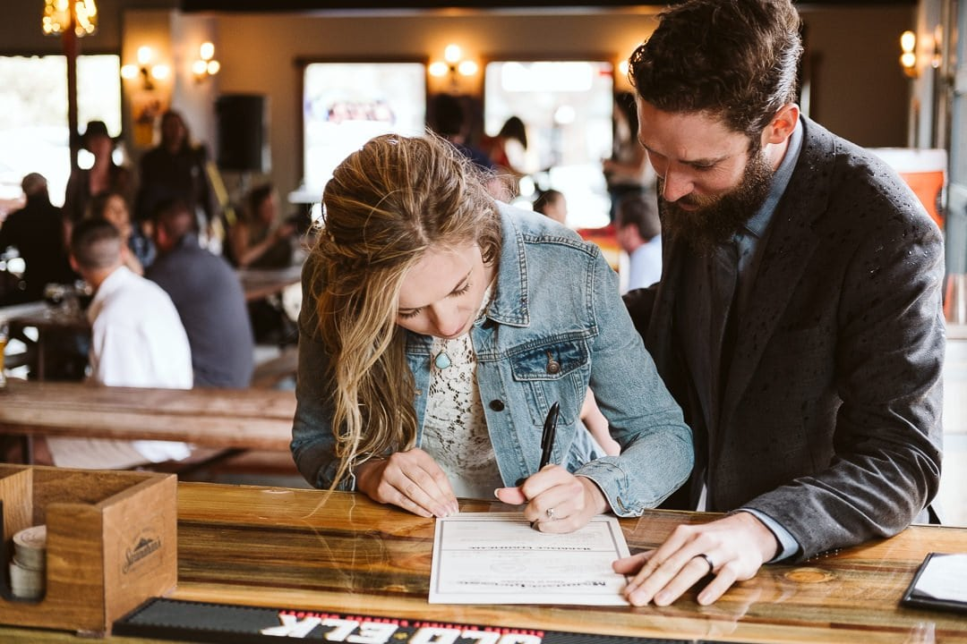 Bride and groom signing marriage license at the bar of a brewery for Colorado elopement