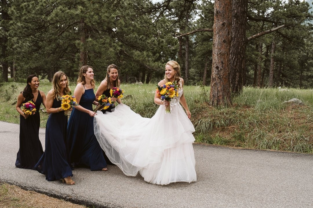 Bride and bridesmaids walking on Flagstaff Mountain in Boulder after Sunrise Amphitheater wedding ceremony, Colorado wedding photographer