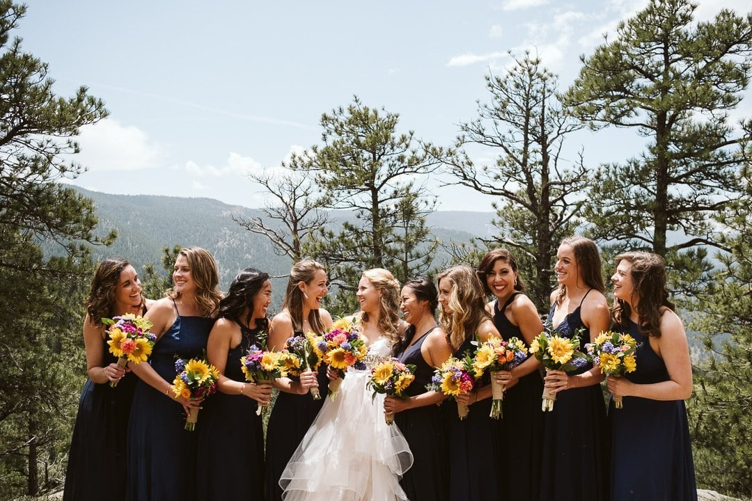 Bride and bridesmaids at Sunrise Amphitheater wedding in Boulder Colorado, Bride in BHLDN dress with bridesmaids in dark blue dresses