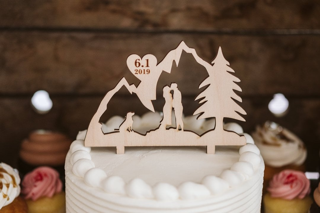 Custom wood cake topper with bride and groom and dog in the mountains