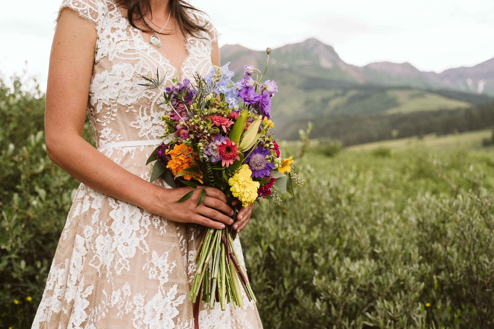Bride with wildflower wedding bouquet in Crested Butte, bride wearing Watters Aella gown