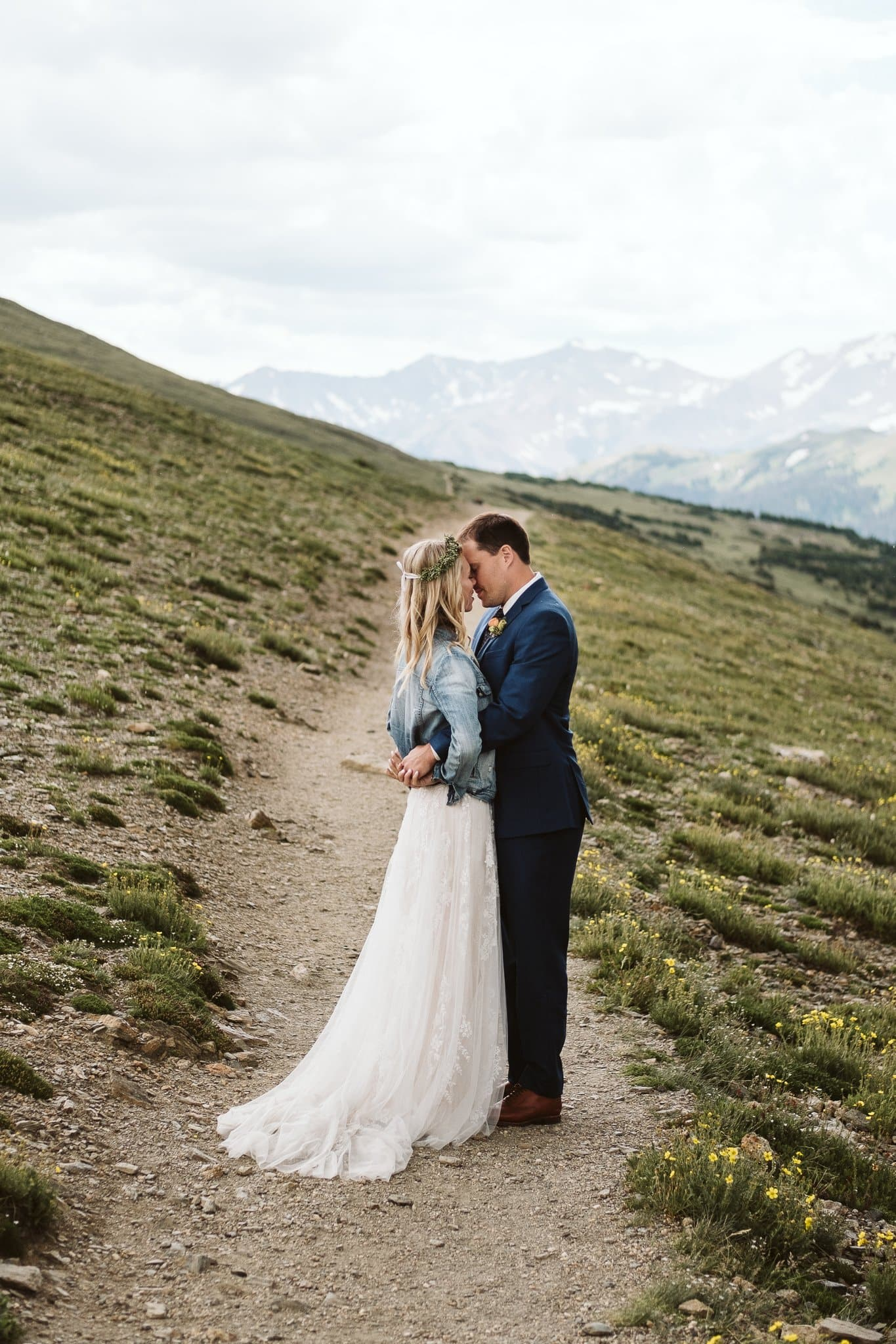 Bride and groom hiking elopement photos at Trail Ridge Road, Rocky Mountain National Park wedding, bride in denim jacket and wedding dress