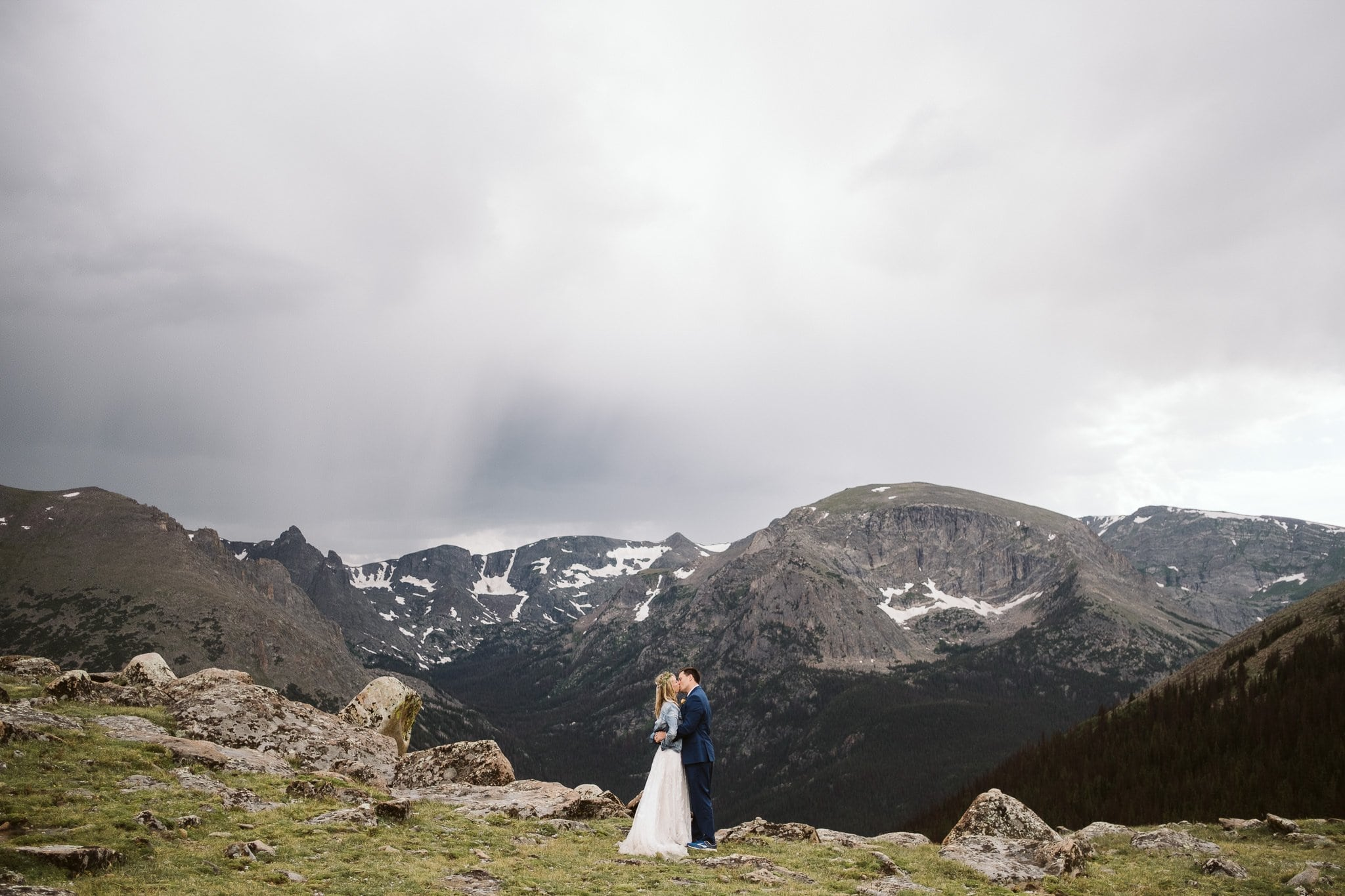 Bride and groom hiking elopement photos at Trail Ridge Road, Rocky Mountain National Park wedding, bride in denim jacket and wedding dress, Colorado elopement photographer