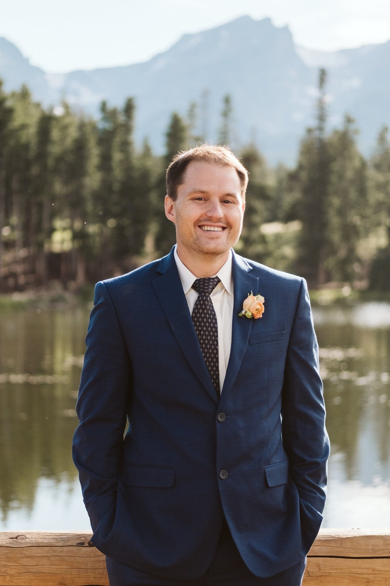 Groom in dark blue suit with orange floral boutonniere at Rocky Mountain National Park elopement at Sprague Lake
