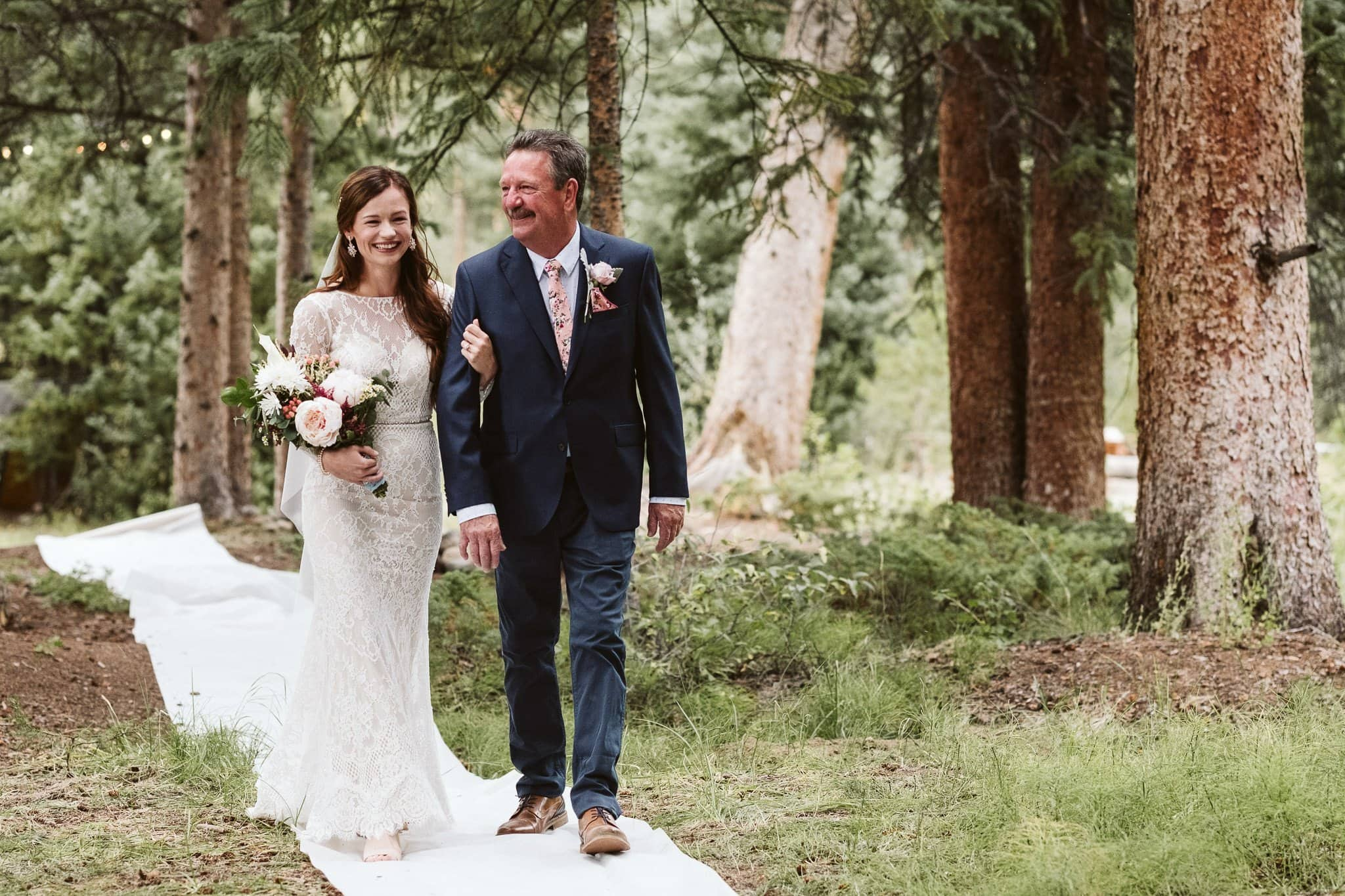 Bride and her father walking down the trail for a wedding ceremony in the woods, Rivertree Lodge in Breckenridge wedding