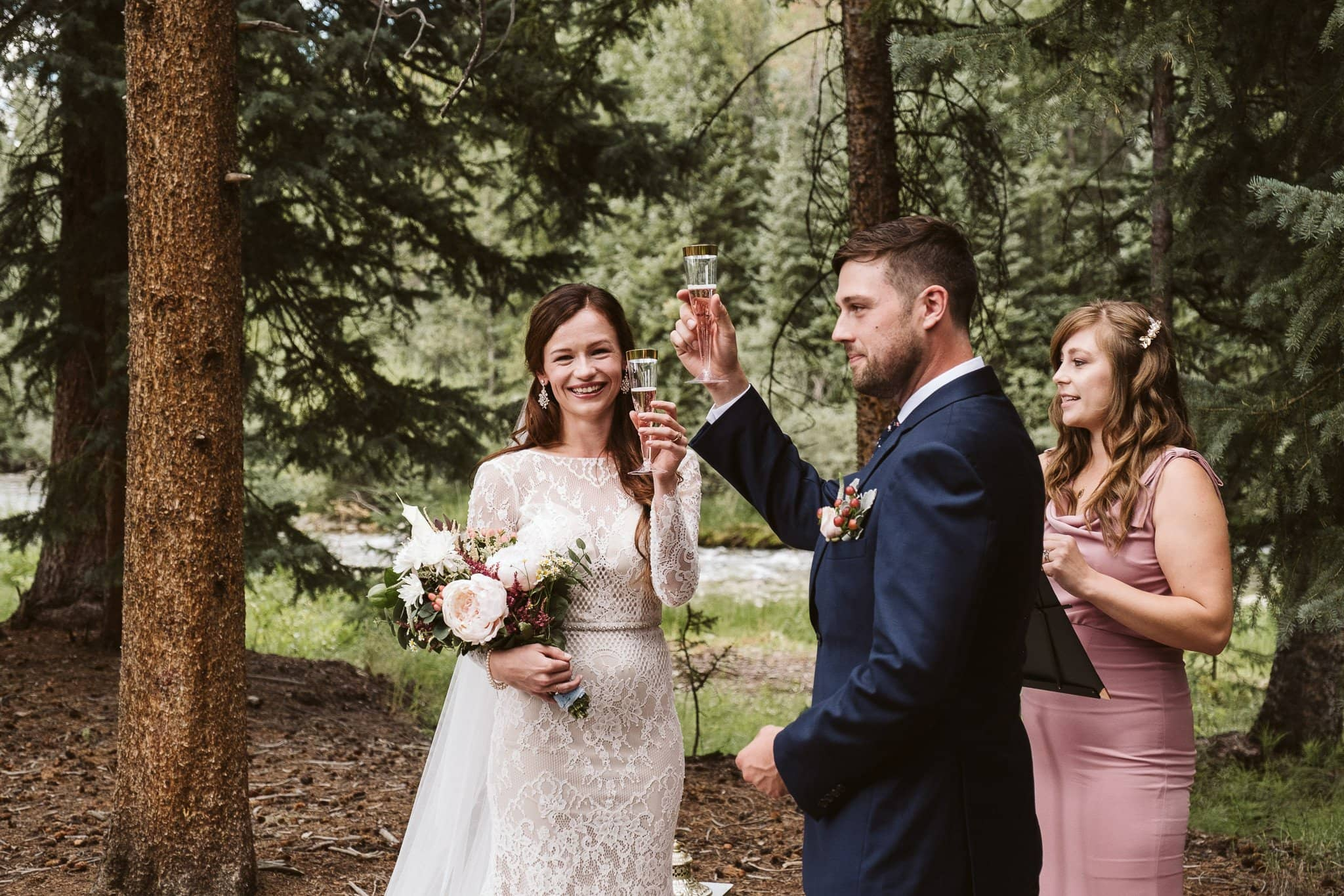 Bride and groom share a champagne toast at their wedding ceremony in the woods