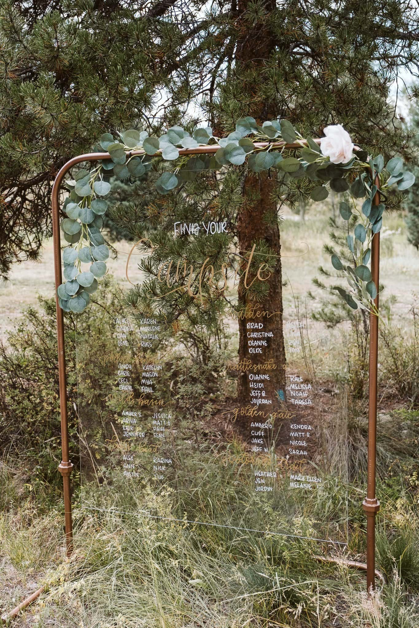 Wedding reception table chart on clear glass and copper frame with camping themed table names
