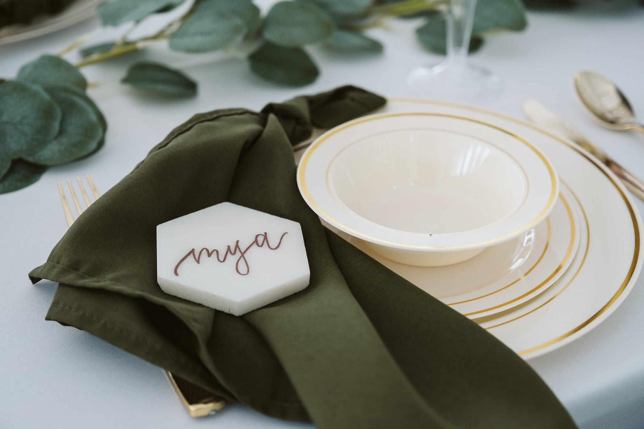 Wedding reception decor with dark green napkins and hexagonal shaped marble with gold calligraphy