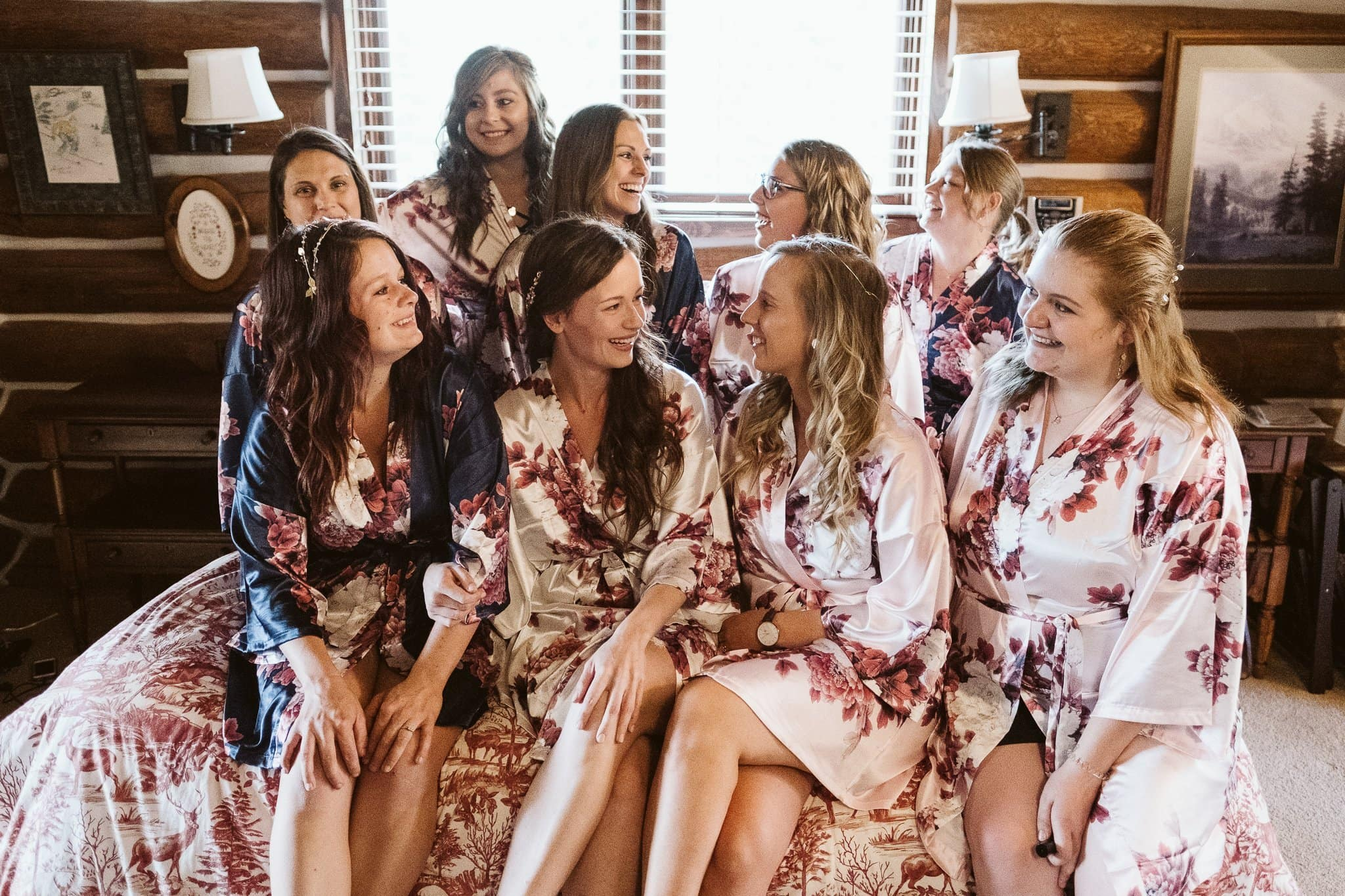 Bride and bridesmaids in matching robes on bed