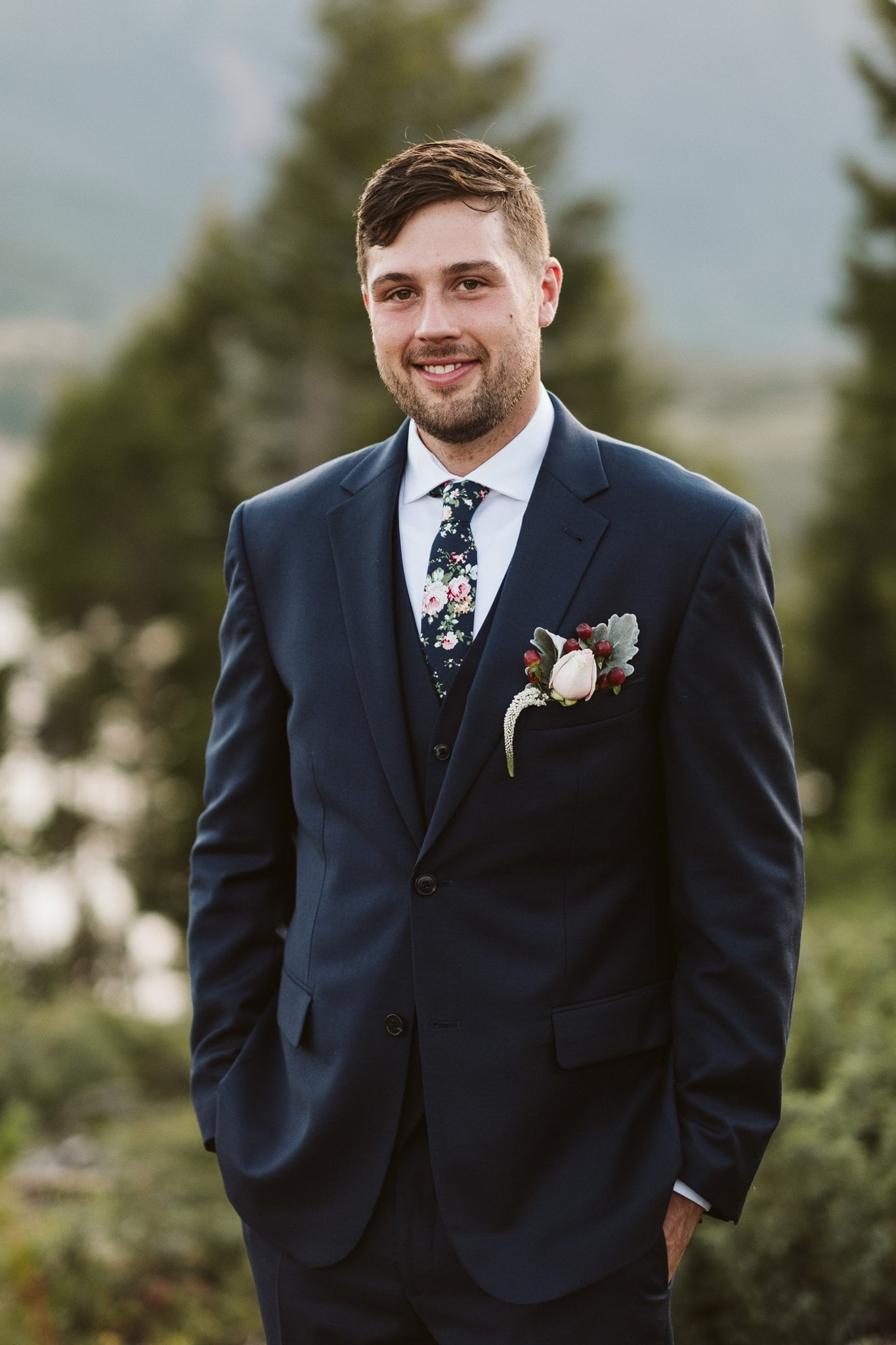 Groom wearing dark blue suit with vest and floral tie