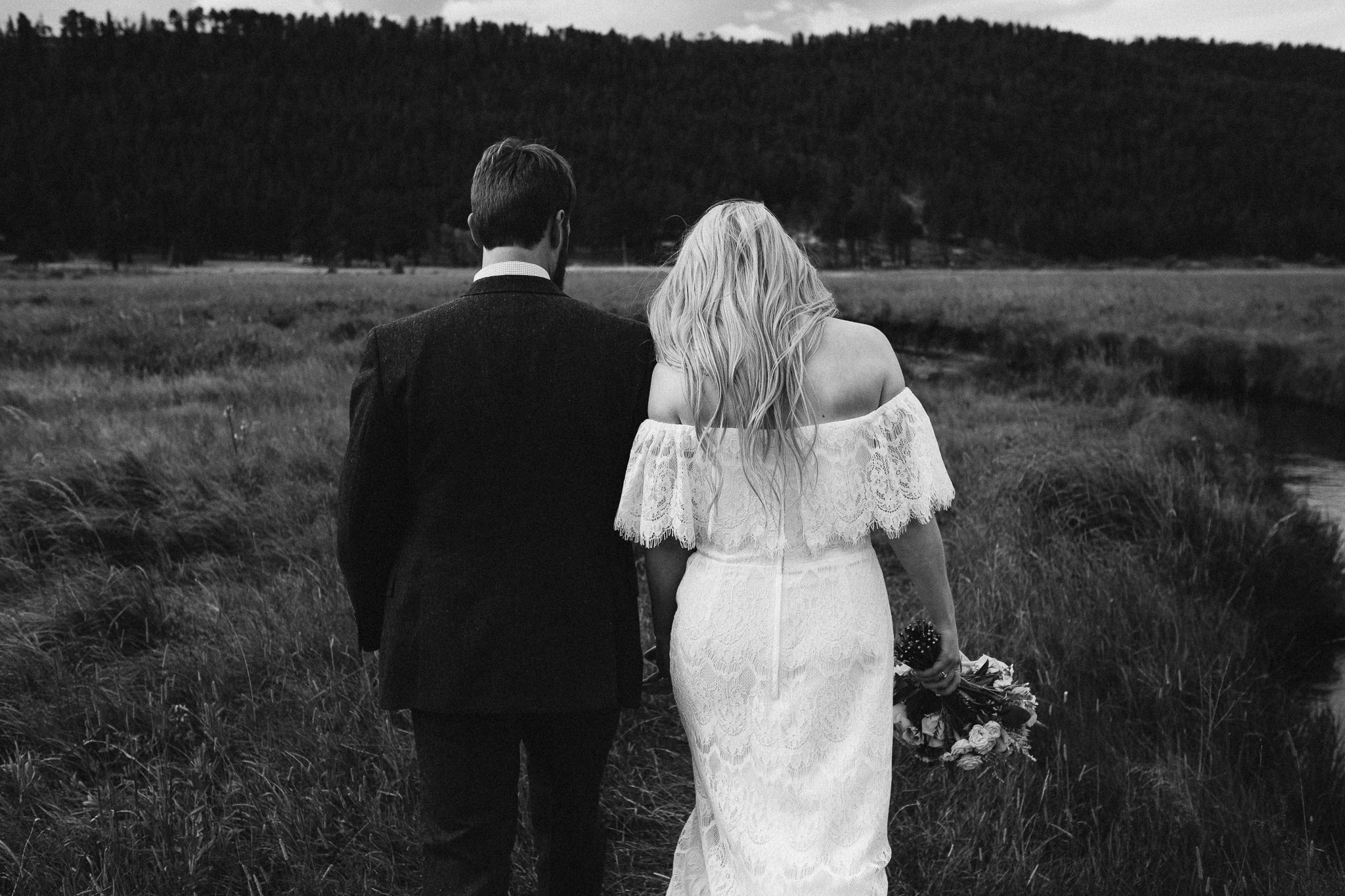 Bride and groom walking away from camera.